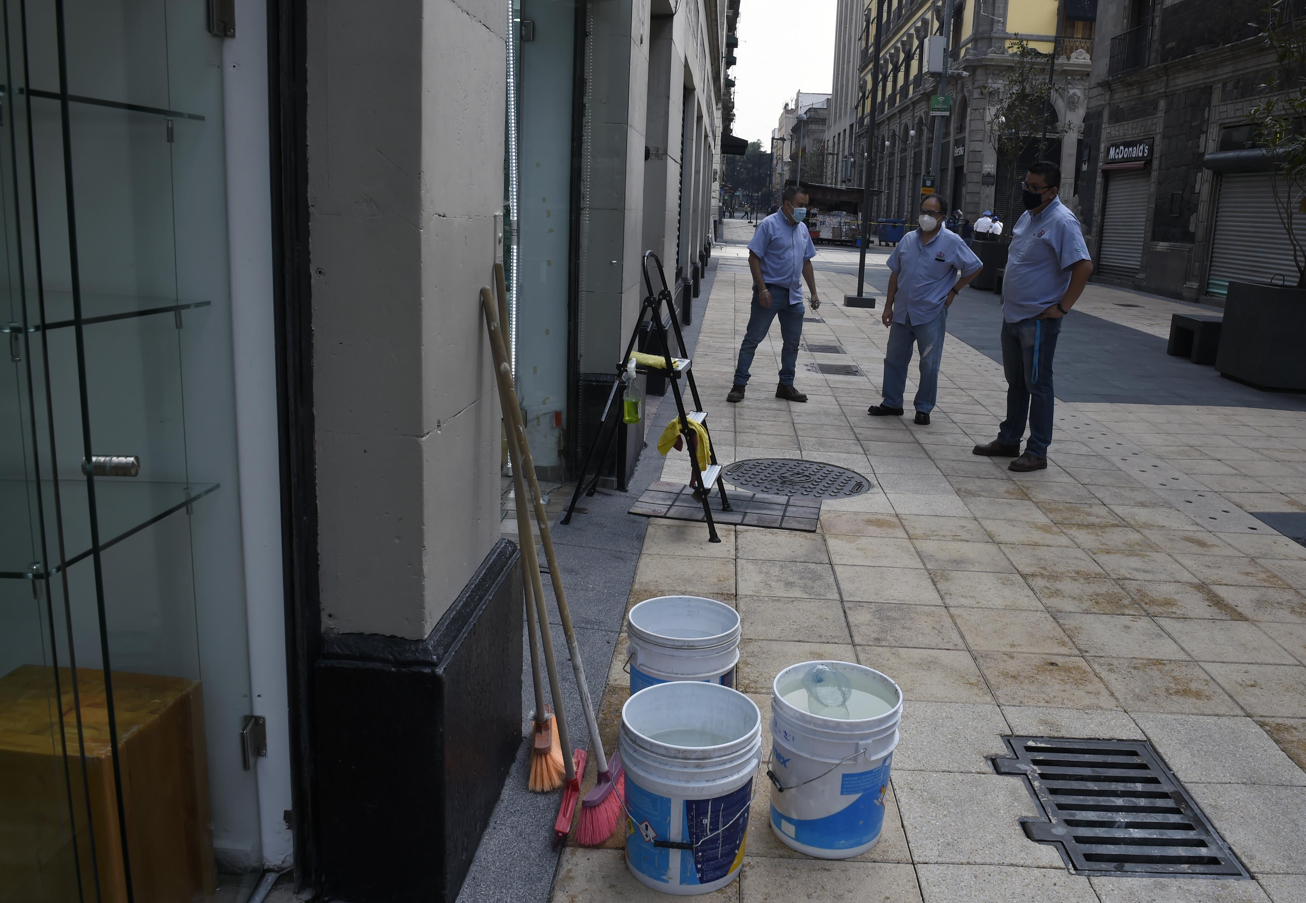 Los empleados limpian la óptica antes de volver a abrir en la Ciudad de México el 29 de junio de 2020 durante la pandemia COVID-19. (Foto: ALFREDO ESTRELLA / AFP)