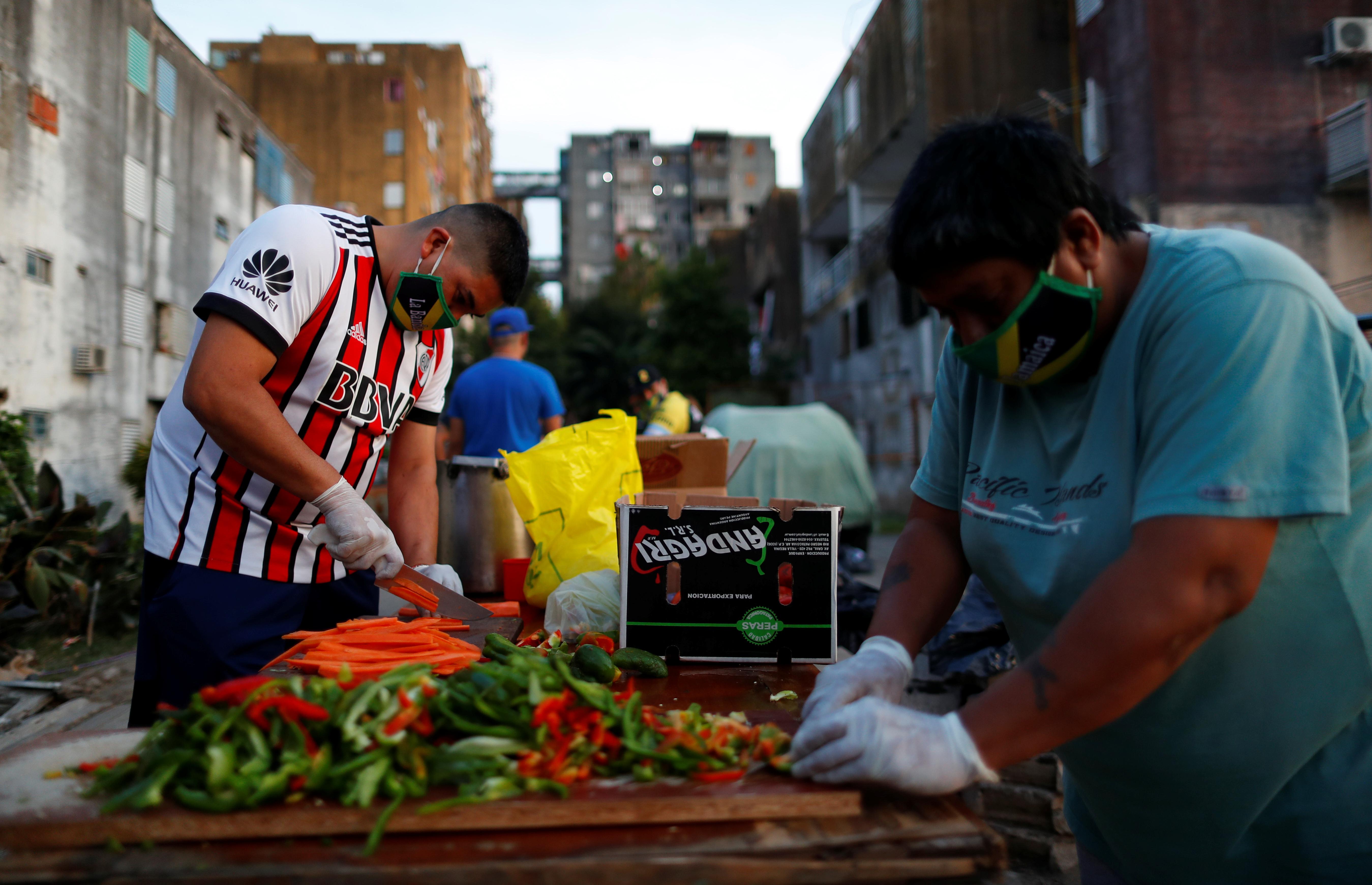 Un grupo de hombres de Fuerte Apache corta verduras para una olla popular. En ese barrio del Gran Buenos Aires, ubicado en el partido de Tres de Febrero, se produjo un hecho que sorprendió gratamente. Ante la llegada del Grupo Táctico de la Policía Bonaerense para patrullar sus calles, los vecinos los comenzaron a aplaudir.