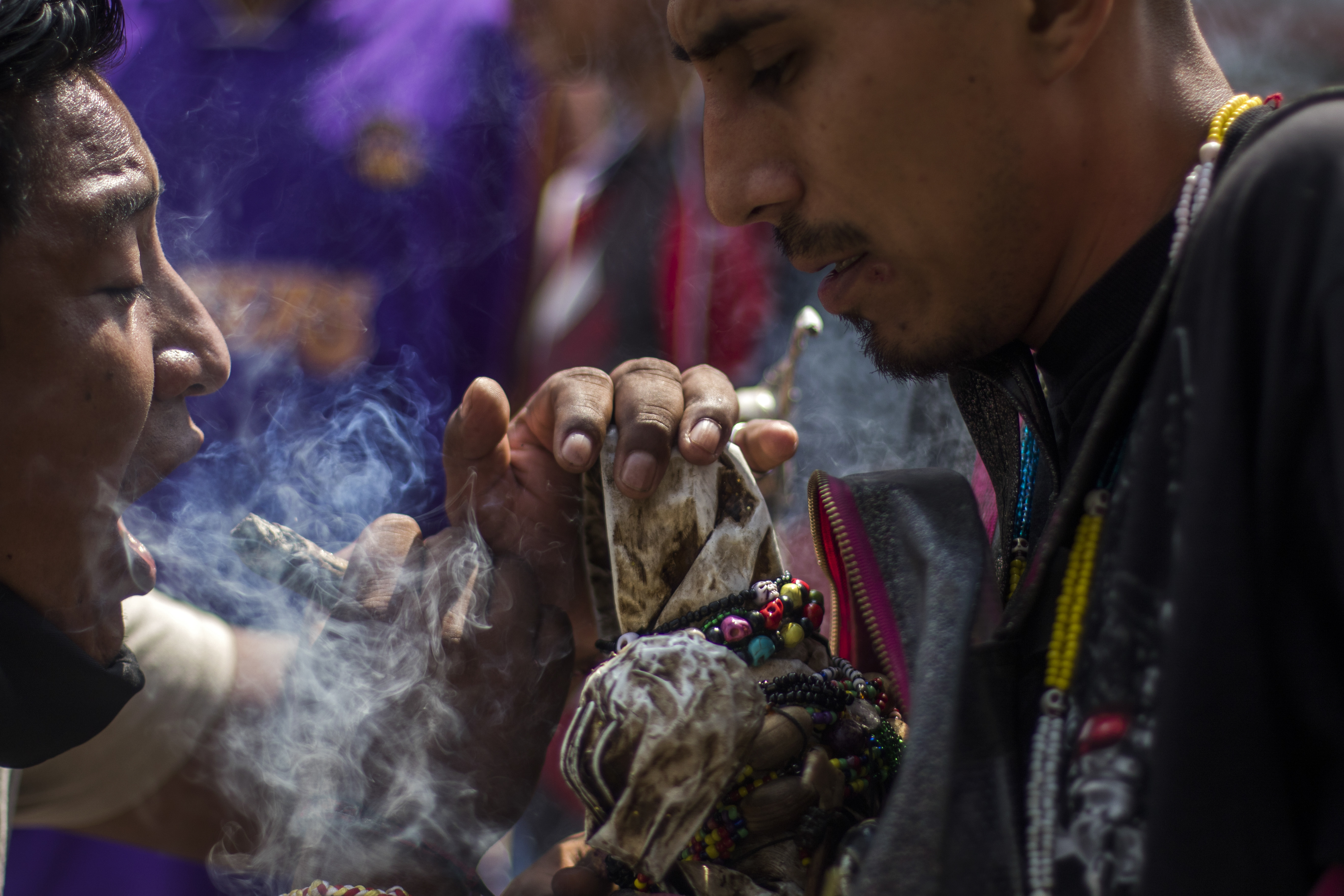 Un hombre sopla el humo de un puro de tabaco a una figura de la Santa Muerte como ritual de limpieza cerca de su santuario en la calle Alfarería, en el barrio de Tepito, de la Ciudad de México, el 1 de octubre de 2020