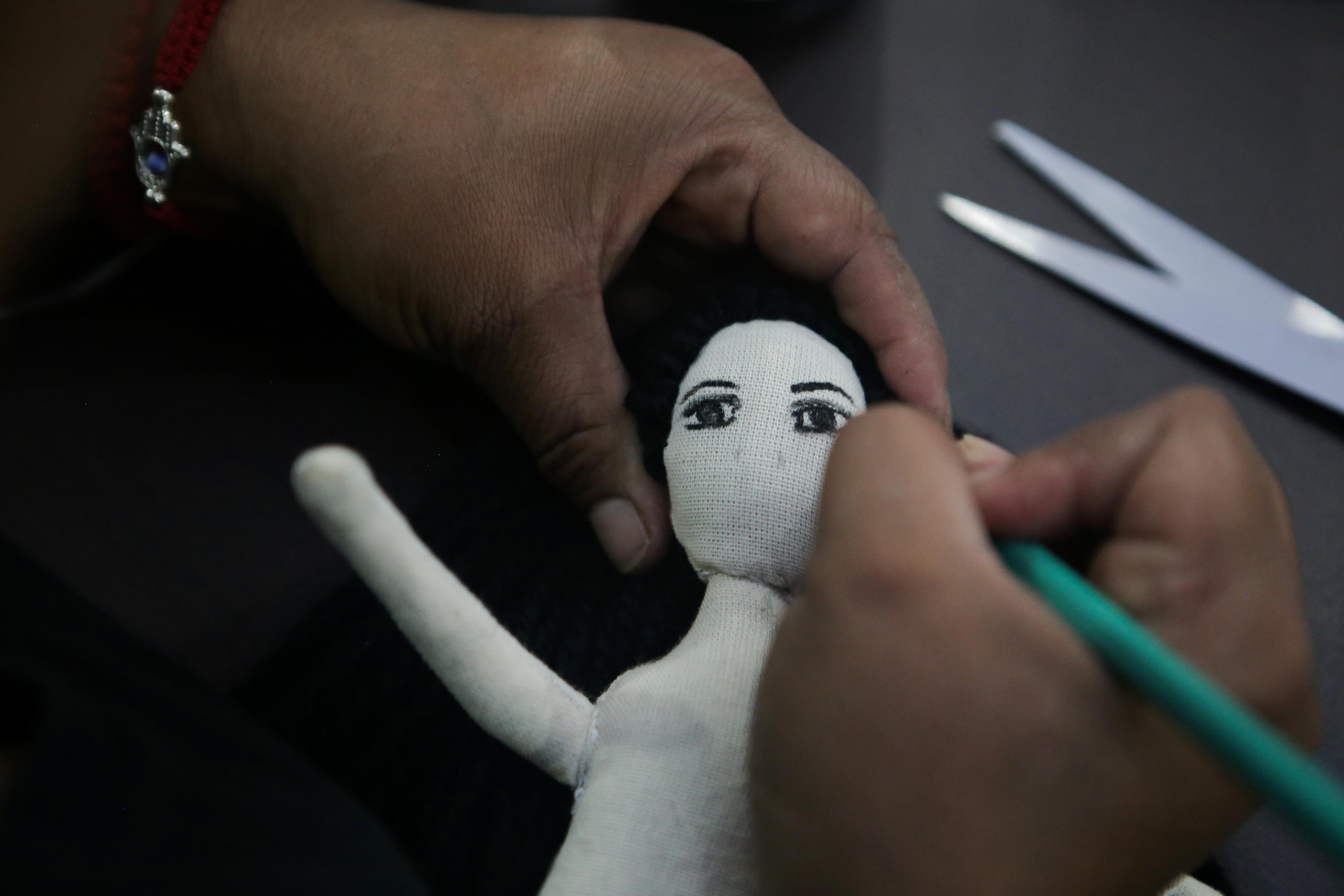 Erika Martínez, madre de una víctima de violencia de género y activista feminista, pinta el rostro de una muñeca de tela dentro de las instalaciones del edificio de la Comisión Nacional de Derechos Humanos, en apoyo a víctimas de violencia de género, en la Ciudad de México, México 10 de septiembre de 2020. Foto tomada el 10 de septiembre de 2020.