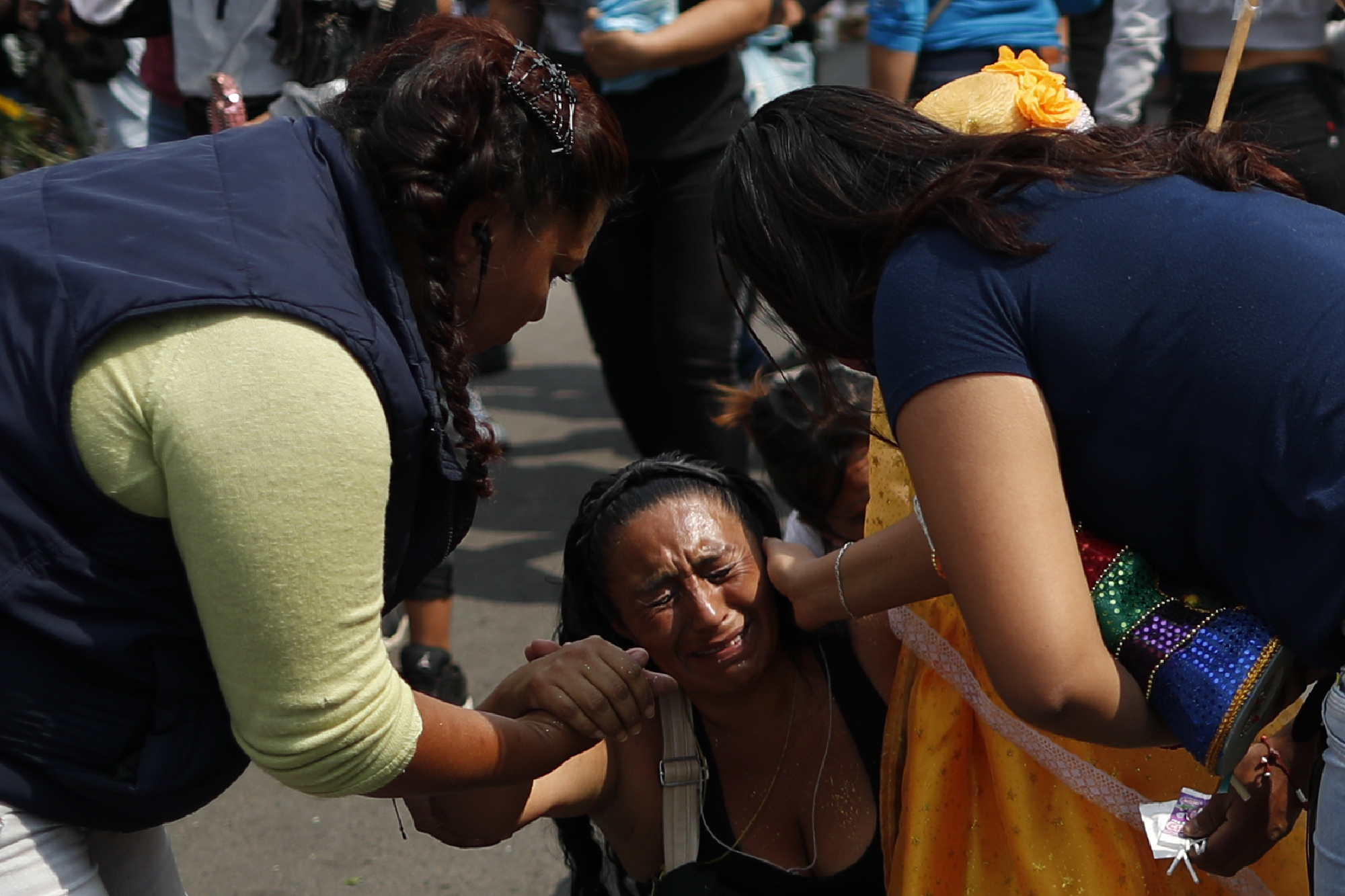 Un transeúnte, a la derecha, se detiene para ofrecer consuelo a Victoria Moreno, de 43 años, mientras lucha por llegar de rodillas al altar de la Santa Muerte (Foto: AP / Rebecca Blackwell)