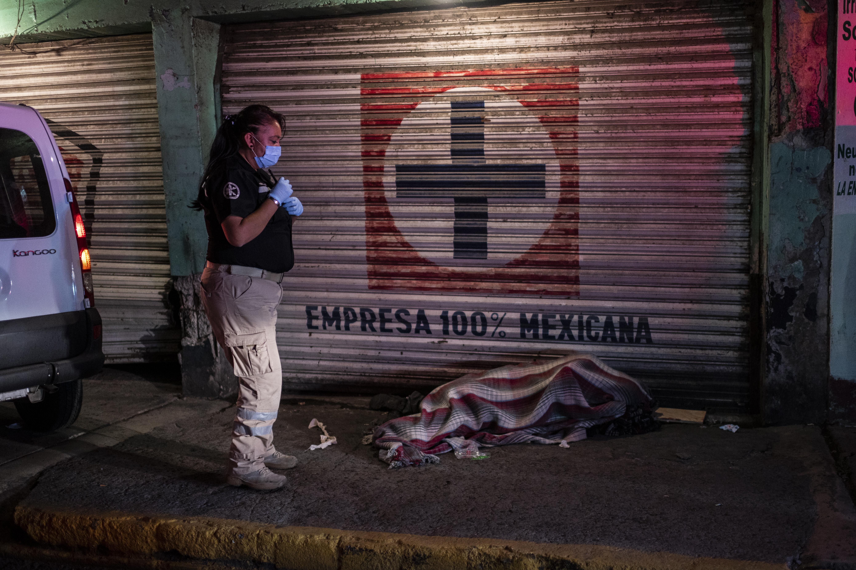 El paramédico Mydori Carmona, de 38 años, revisa a un hombre sin hogar que fue atropellado temprano en la mañana del 20 de junio de 2020 en Ciudad Nezahualcóyotl, Estado de México, México, durante la nueva pandemia de coronavirus COVID-19. (Foto por Pedro PARDO / AFP)