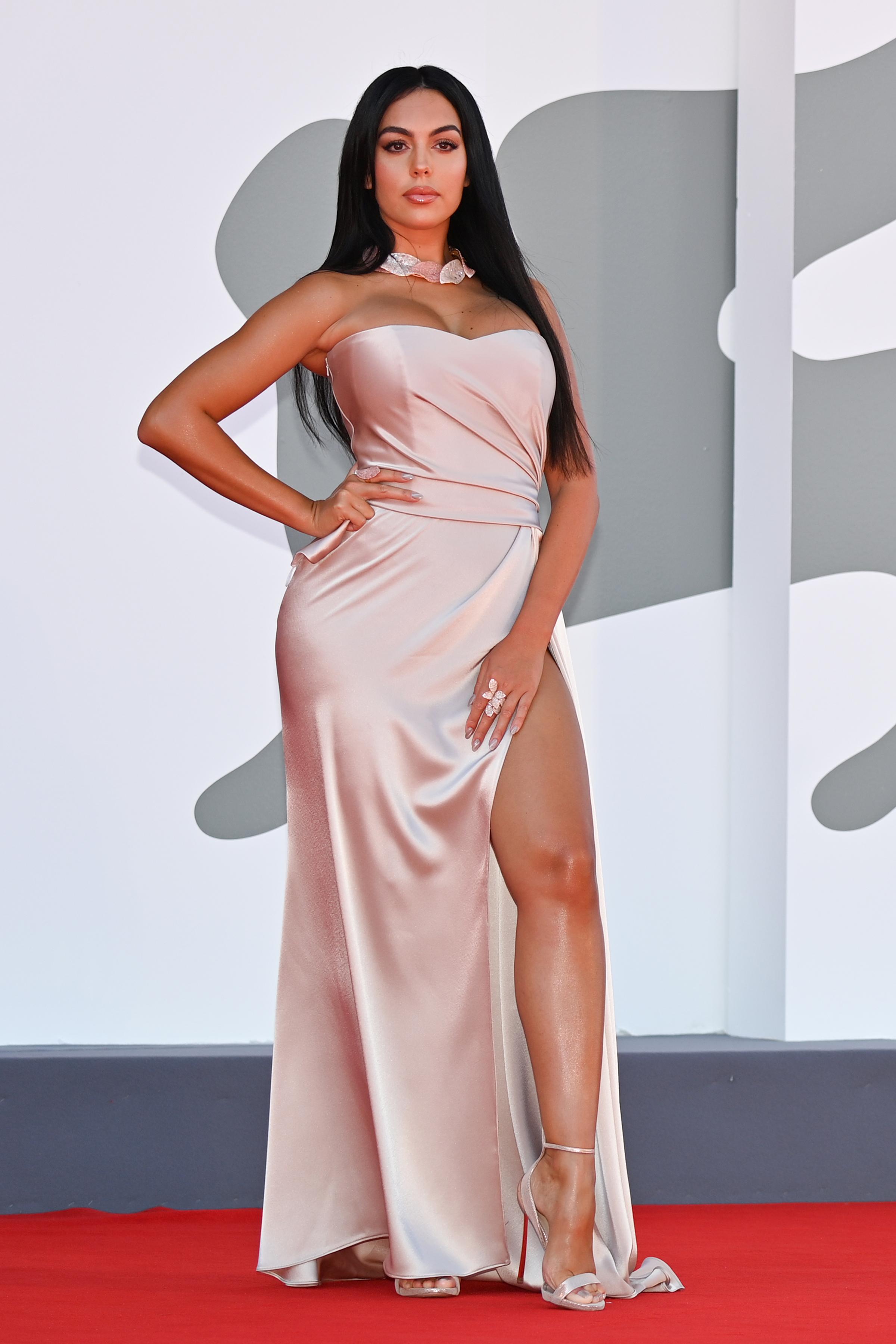Georgina Rodríguez optó por un vestido con escote corazón en color rosa pastel, con drapeado en la cintura, y un gran tajo en la falda. Comlpetó su look con sandalias de Jimmy Choo a tono y joyas en oro rosado