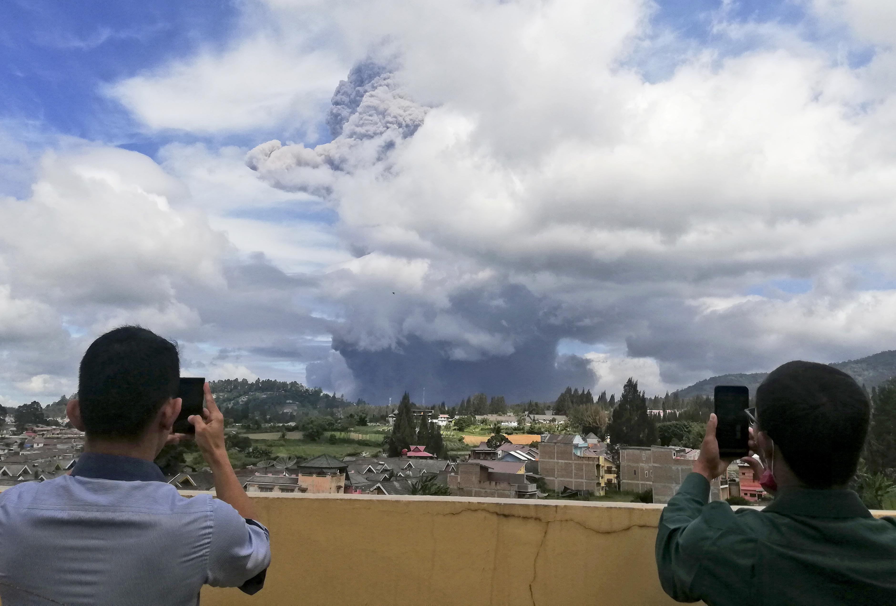 Dos personas toman fotos al volcán Sinabung mientras hace erupción en Karo, Indonesia, el lunes 10 de agosto de 2020. (AP Foto/Sugeng Nuryono)