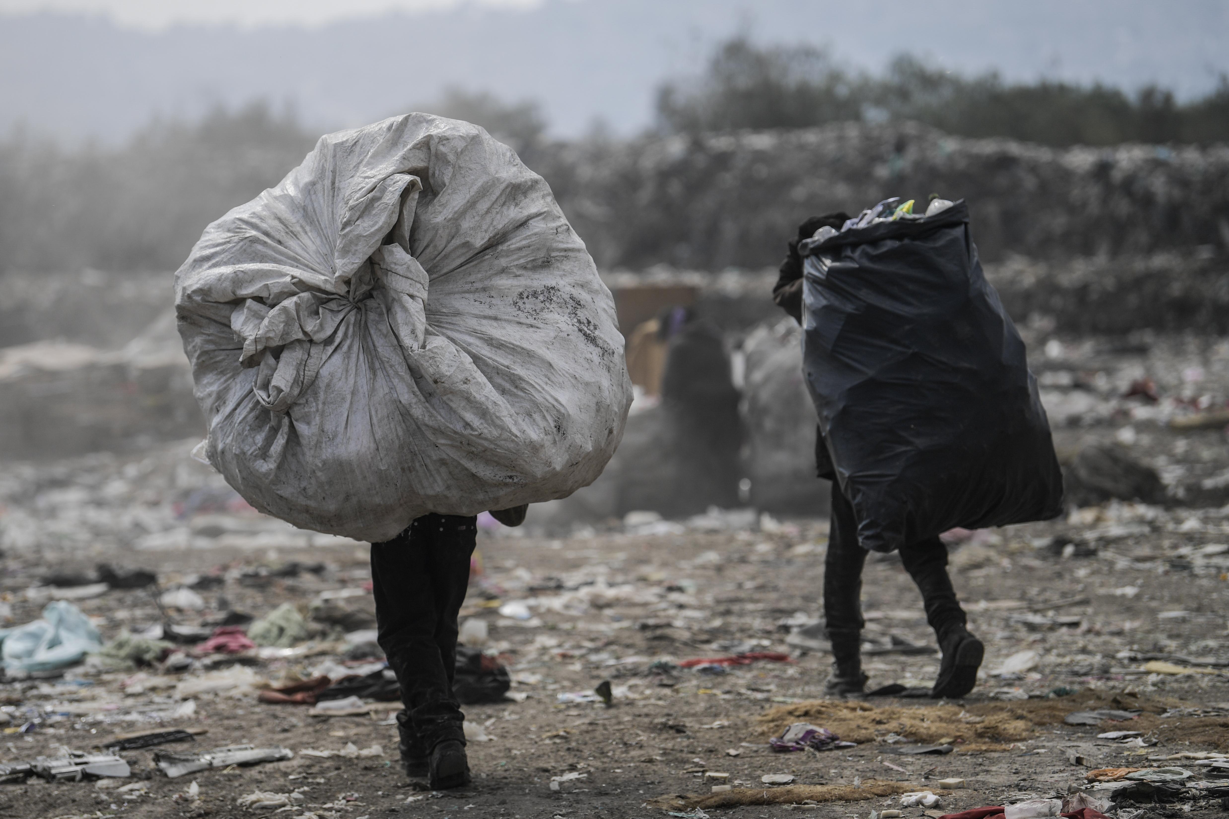 Los recolectores llevan bolsas en el basurero