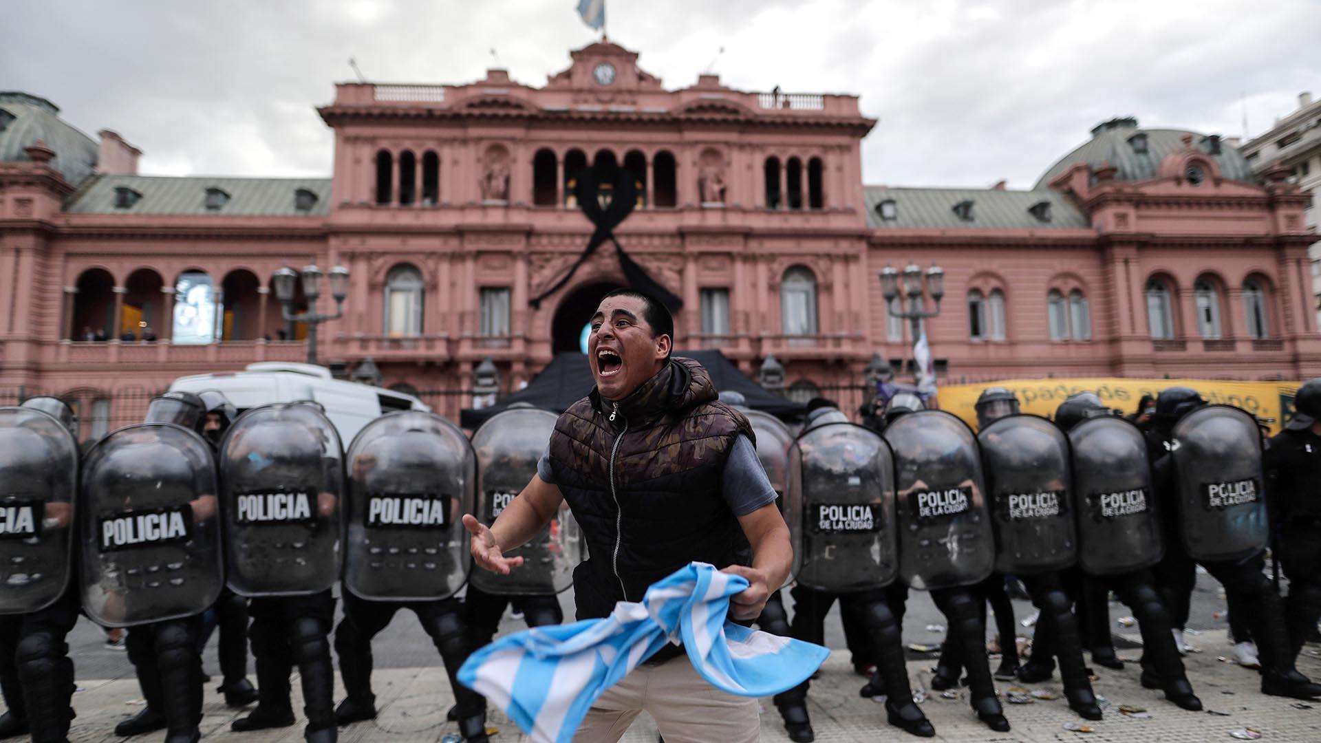 Un seguidor ante un grupo de efectivos de la Policía a las puertas de la Casa Rosada