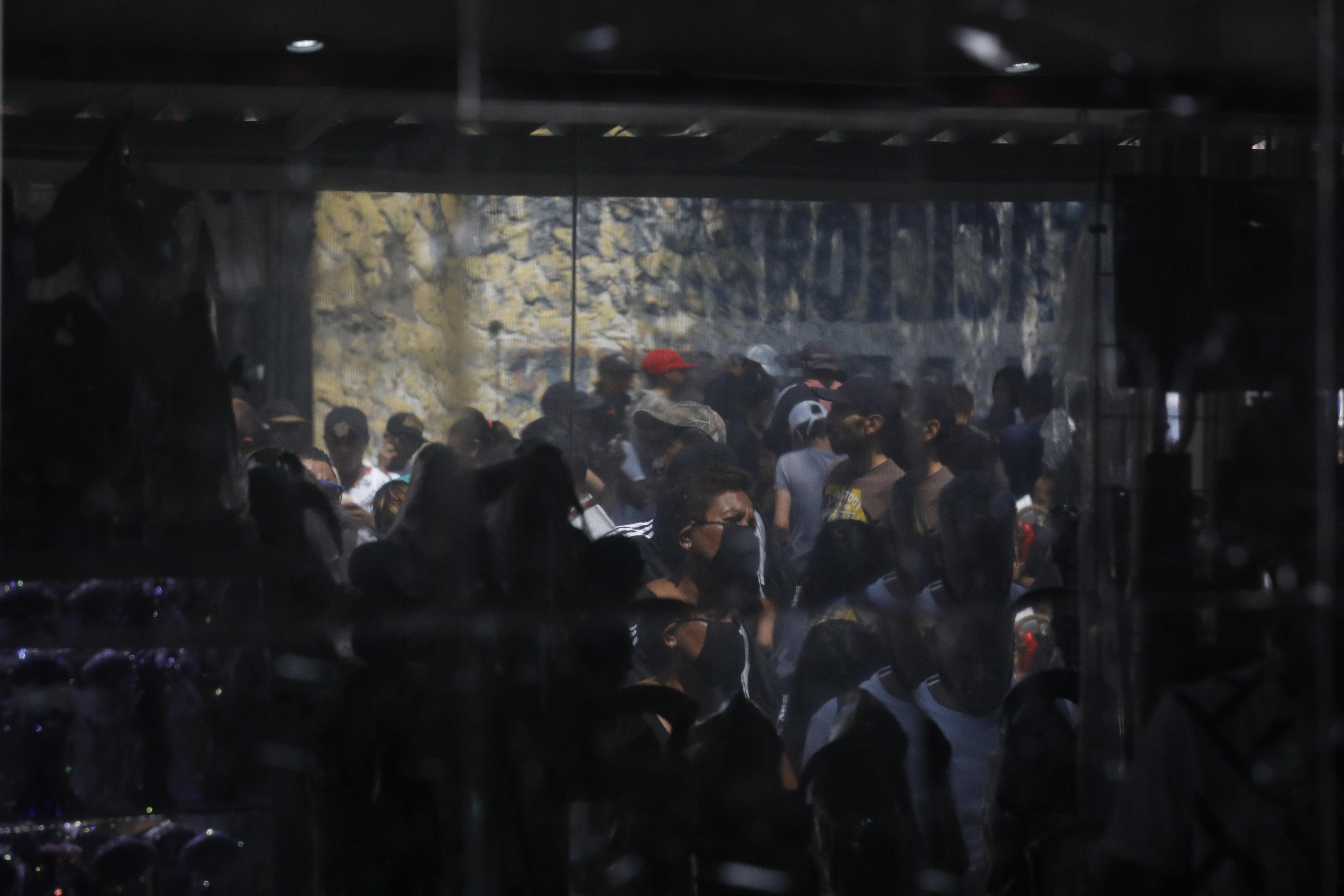Las personas se reflejan en una pared mientras esperan afuera para visitar un altar a la Santa Muerte. (Foto: AP / Rebecca Blackwell)