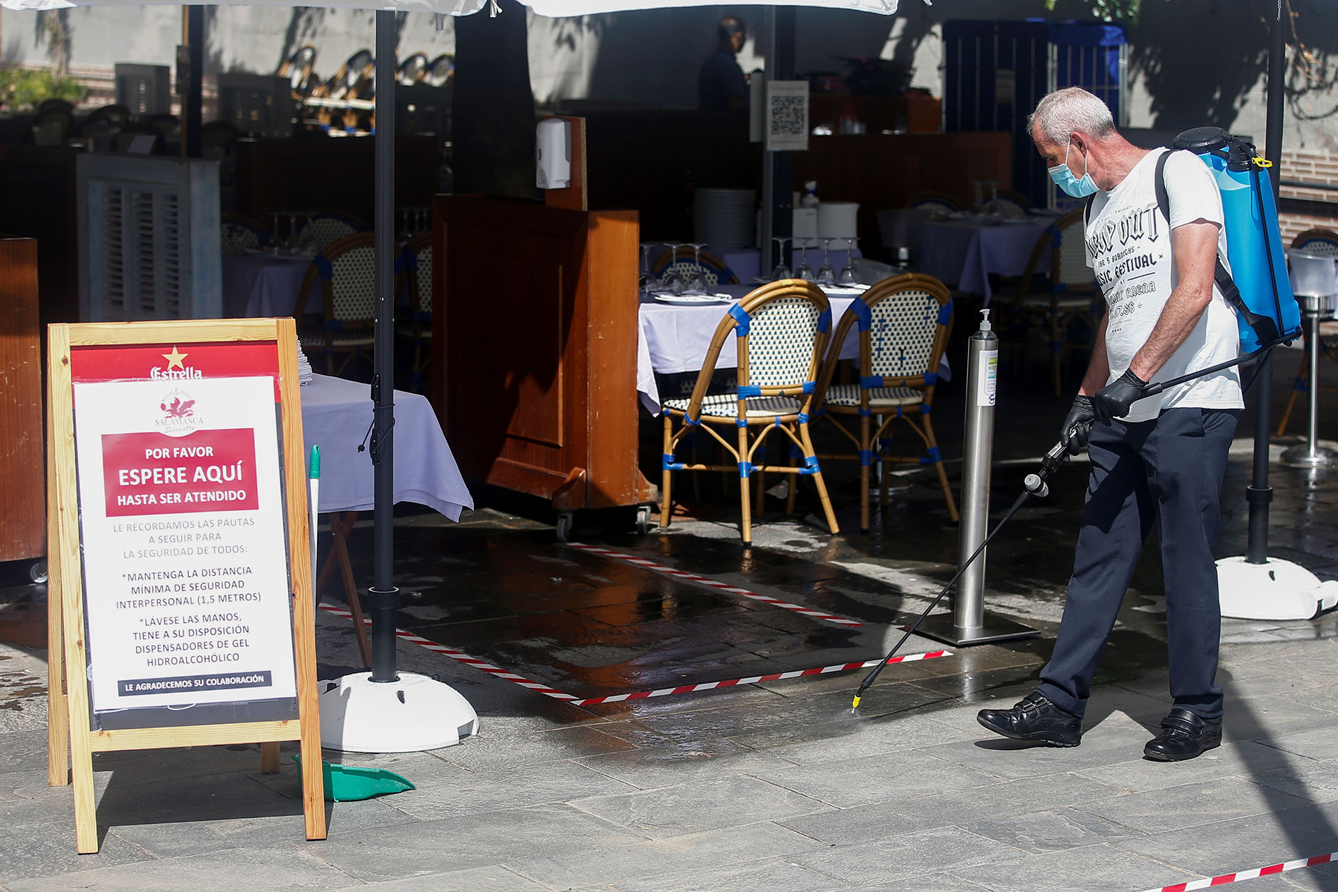 Un trabajador desinfecta la terraza de un bar en la Barceloneta. (EFE/Quique Garcia)