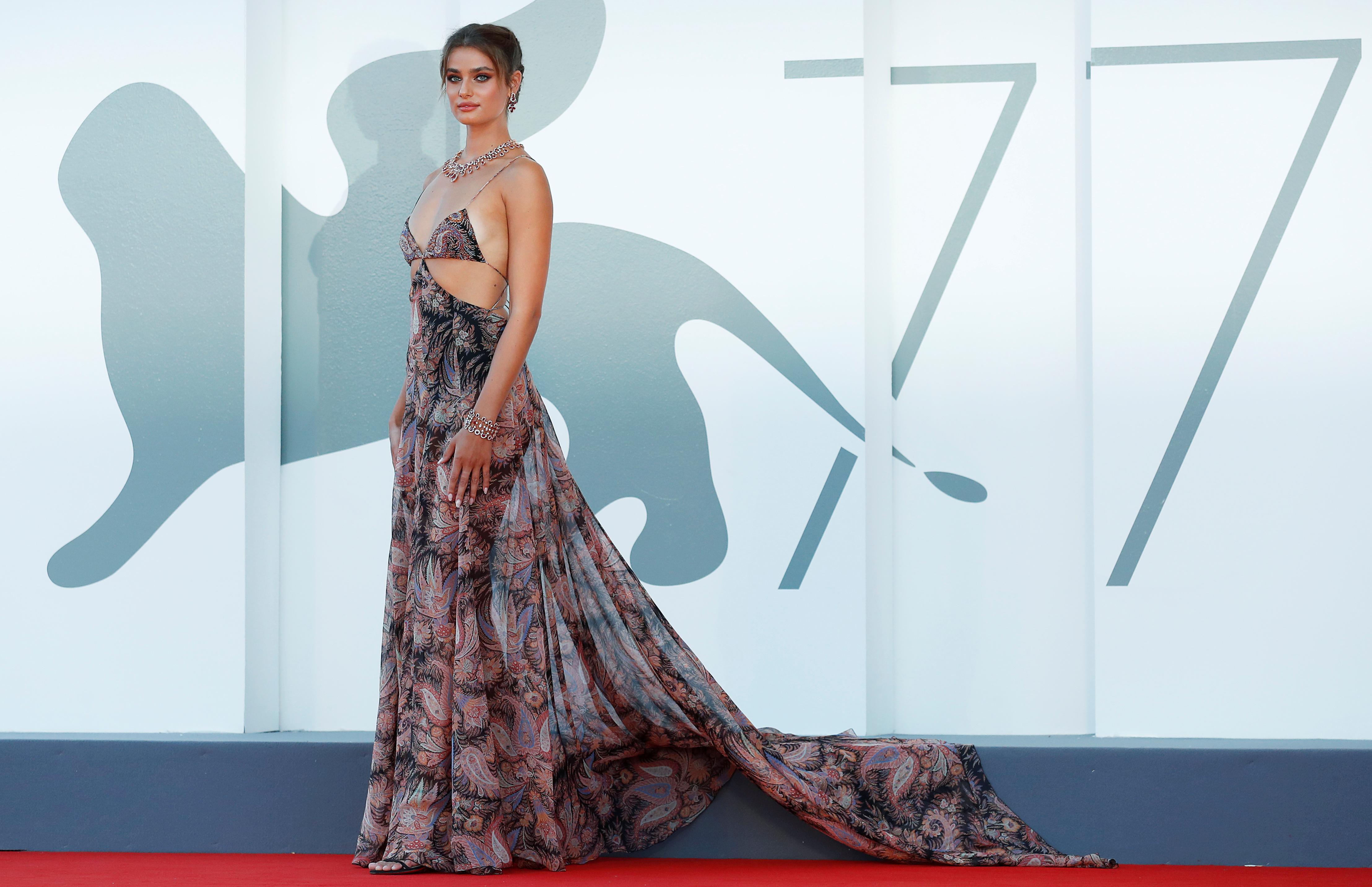 Taylor Hill, también hizo su presencia en la alfombra roja de Venecia y deslumbró con un vestido escotado y con cortes en la cintura con estampados de búlgaros firmado por Etro