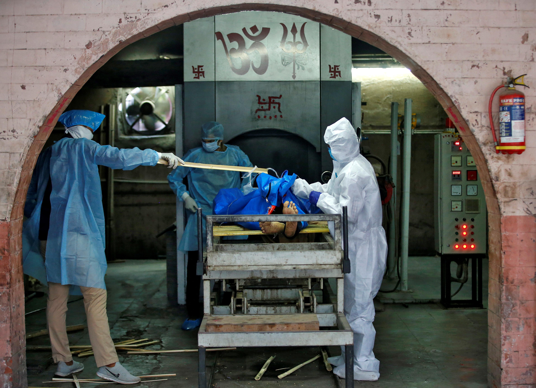 Trabajadores municipales con equipo de protección se preparan para incinerar el cuerpo de un hombre, que murió debido a la enfermedad coronavirus (COVID-19), en un crematorio en Ahmedabad, India, el 22 de abril de 2020. REUTERS/Amit Dave