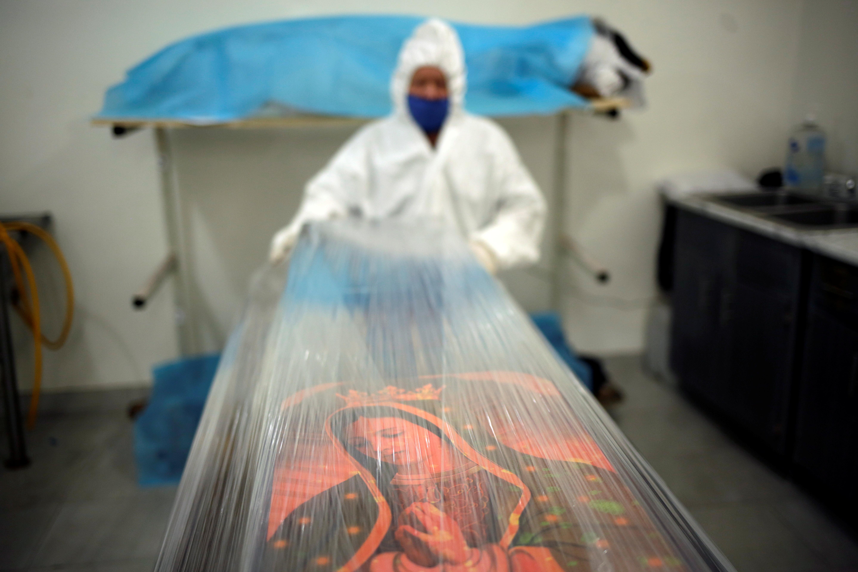 Un empleado de la funeraria Ríos envuelve un ataúd que contiene el cuerpo de una persona que murió por coronavirus (COVID-19) en una película plástica en Ciudad Juárez, México, el 23 de octubre de 2020.