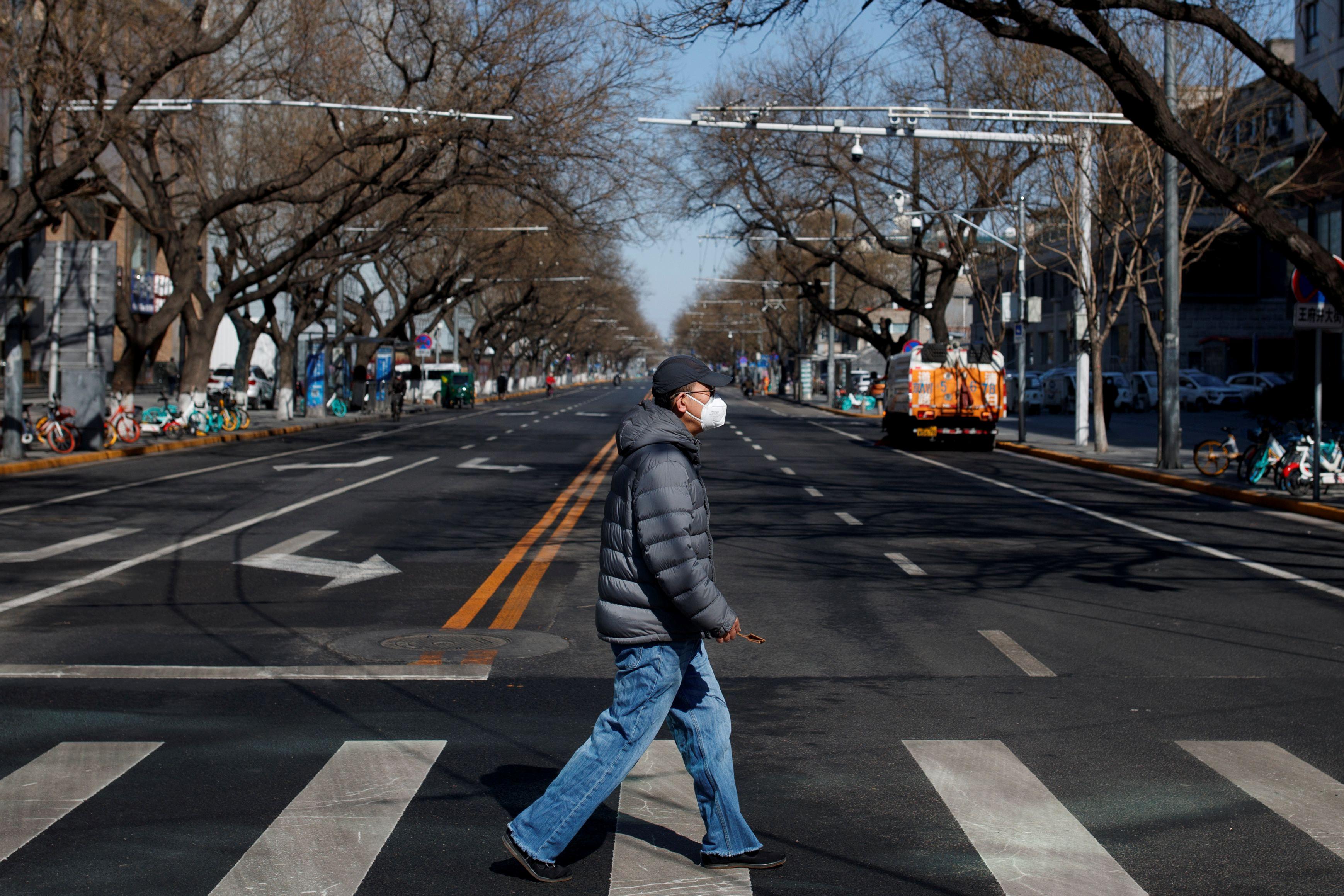 Un hombre cruzando una calle en Beijing, utilizando un barbijo (REUTERS/Thomas Peter/File Photo)