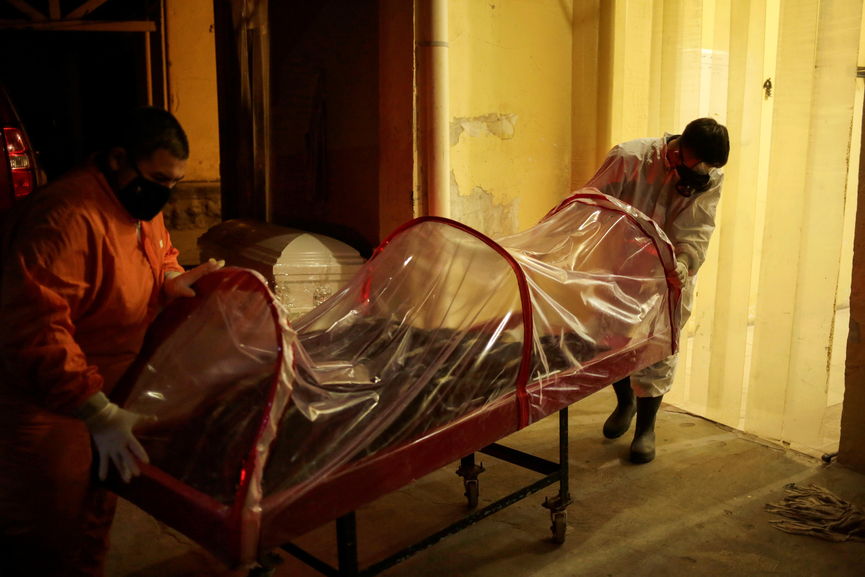 Empleados de la funeraria Ríos trasladan el cuerpo de un hombre, que murió a causa de coronavirus (COVID-19), a sus instalaciones en Ciudad Juárez, México, el 23 de octubre de 2020.
