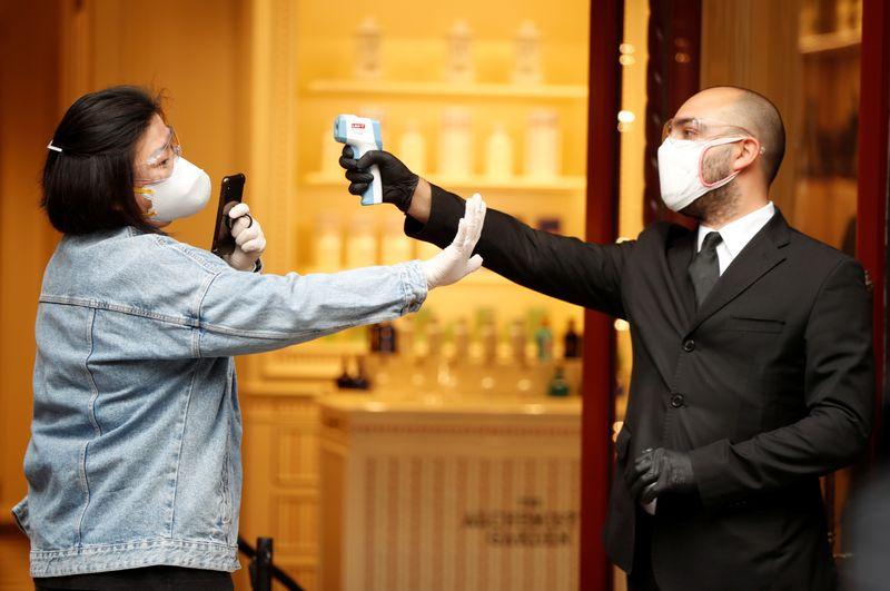 Foto del lunes de un hombre tomando la temperatura de una mujer en Roma tras la relajación de las medidas de confinamiento por el coronavirus [18 de mayo de 2020] (Reuters/ Yara Nardi)