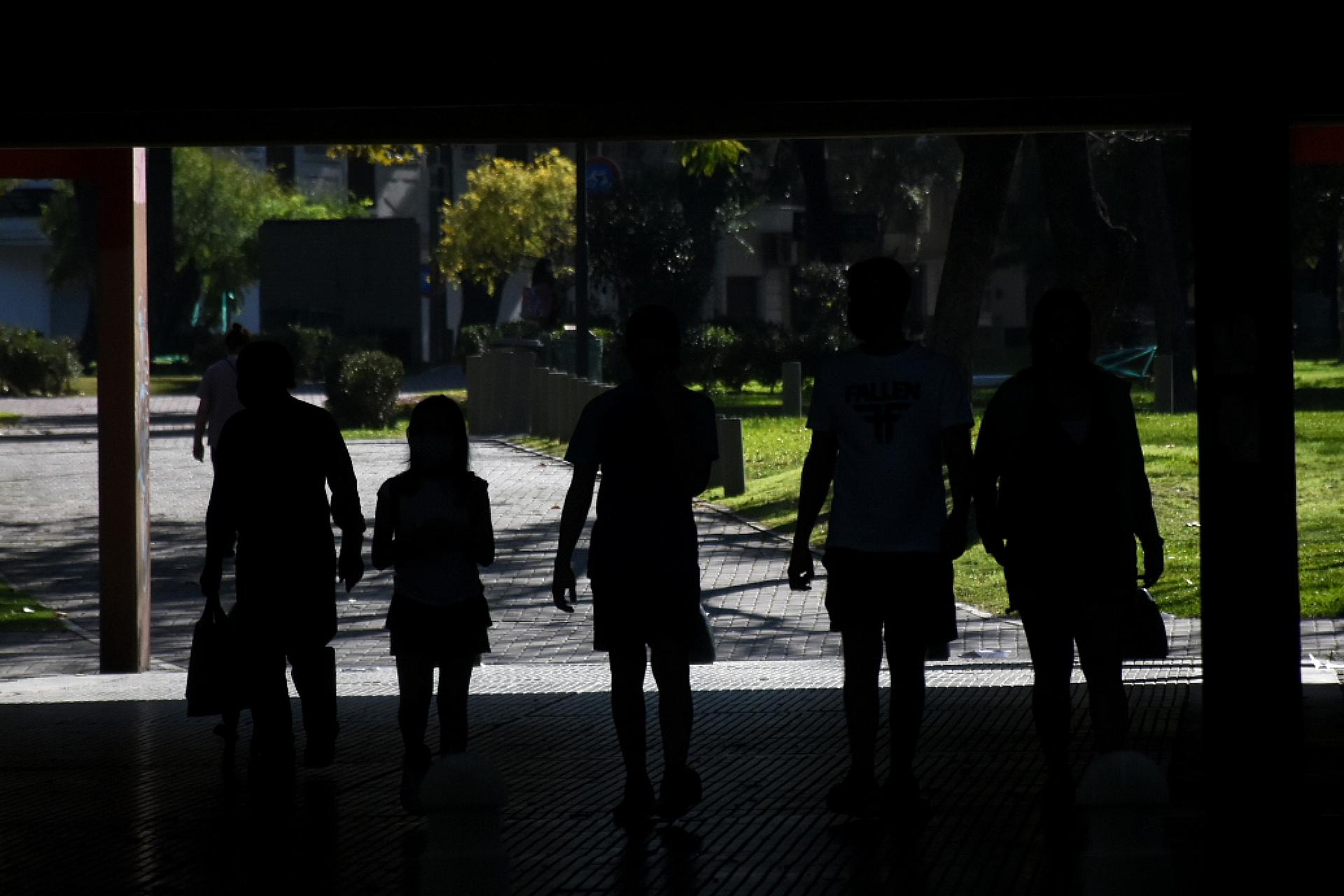 Un grupo de niños, junto a sus padres, en una plaza porteña