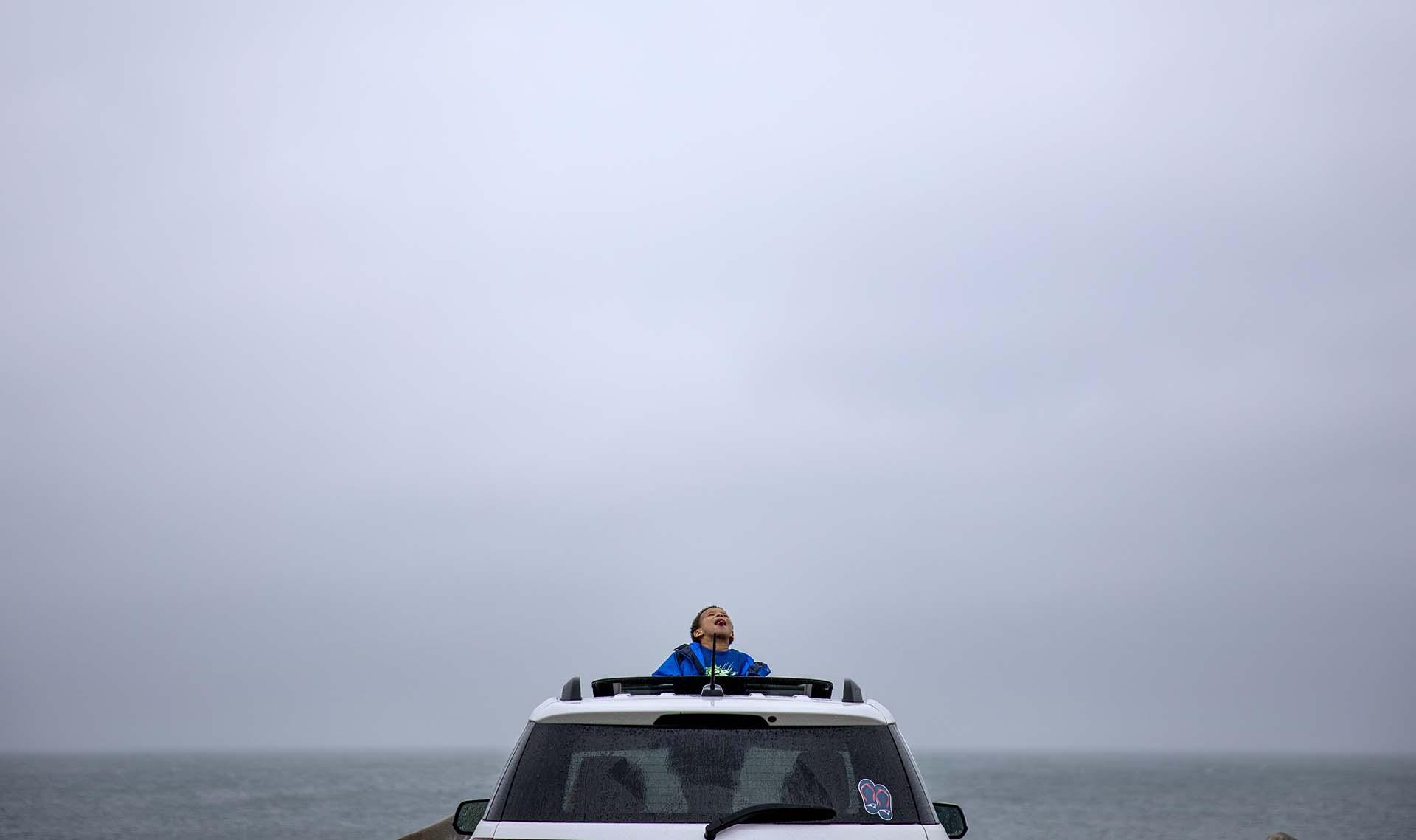 Mason Lambert, de 5 años, mira al cielo mientras la lluvia cae en Narragansett, Rhode Island (AP Photo/David Goldman)