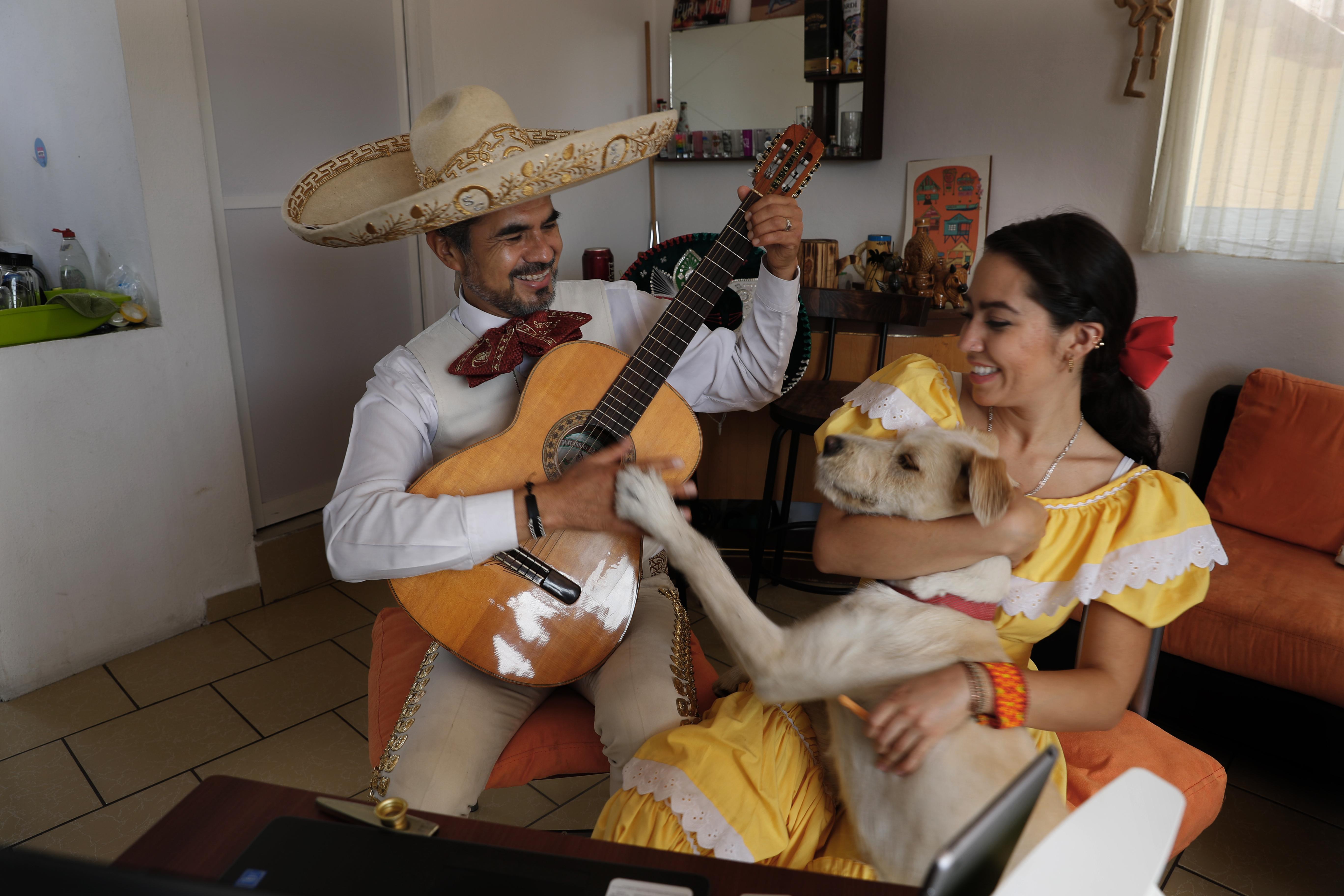 El Mariachi Duo Villa Maria, Sergio Carpio, a la izquierda, y Melissa Villar, acompañados por su perro Güiro, se presentan a través de Internet para un cliente durante el día de las madres. (Foto: AP/Marco Ugarte)