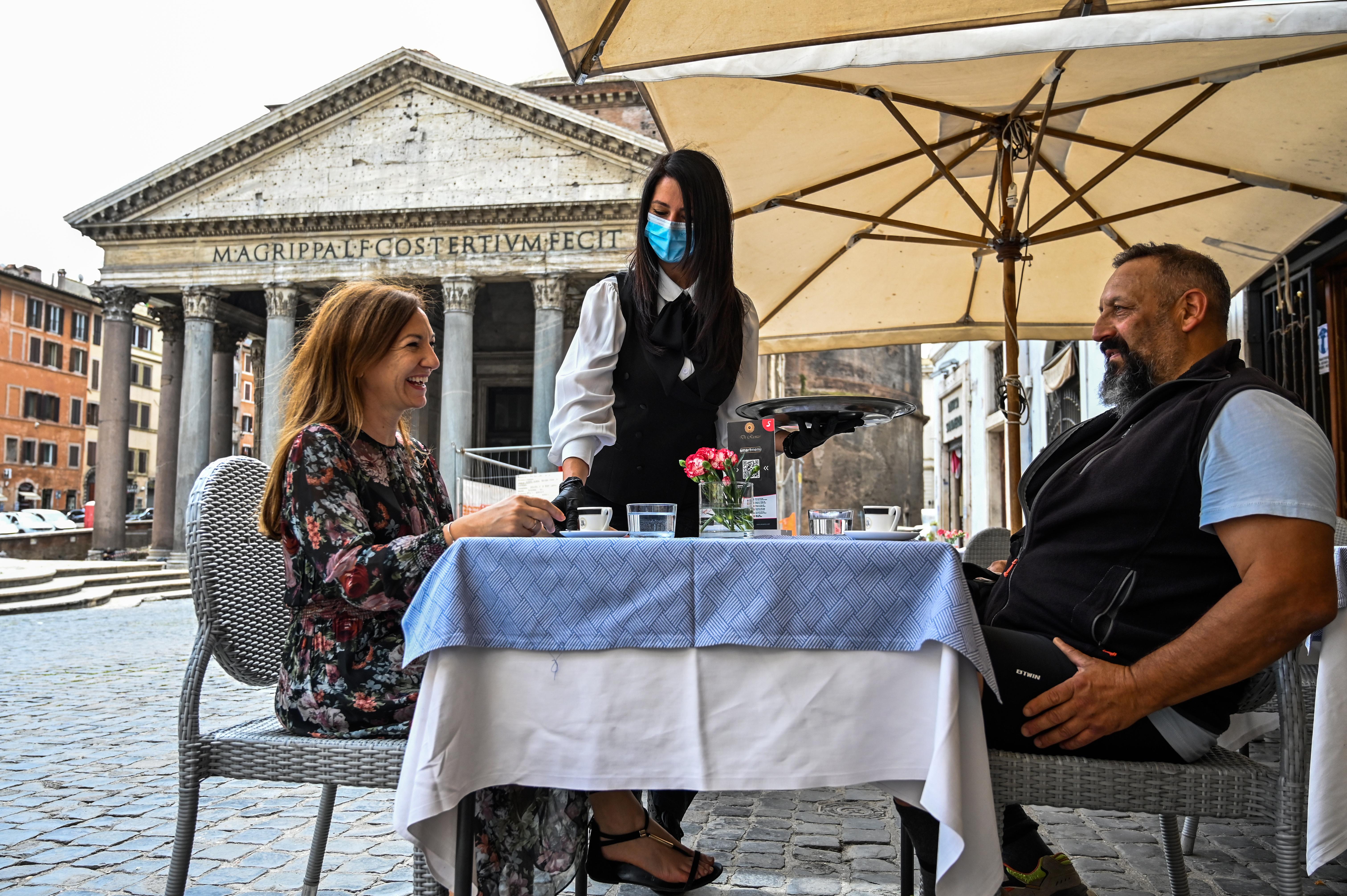 Una camarera sirve a dos clientes en un café frente al Pantheon en Roma (Andreas Solaro/ AFP)