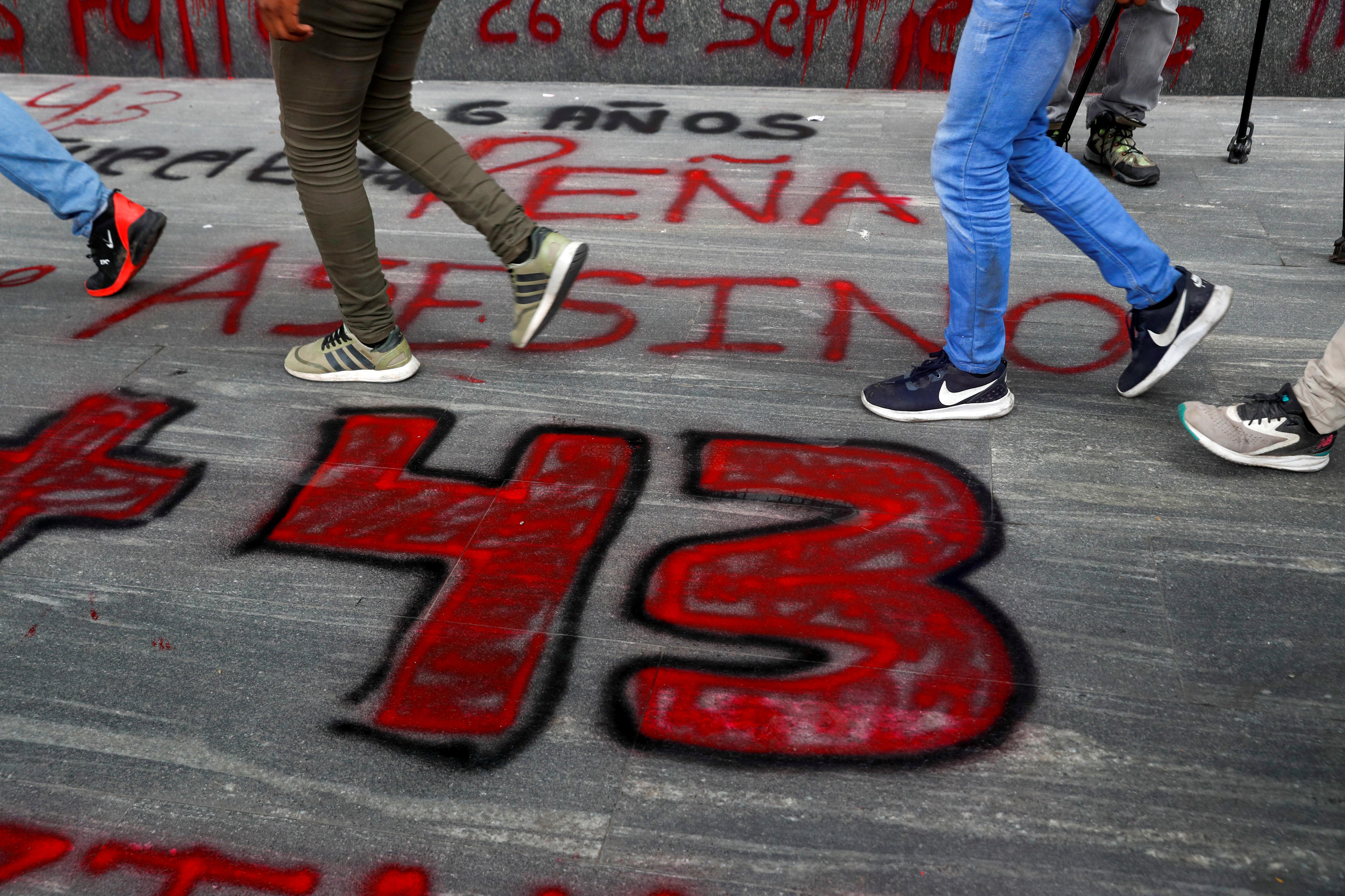 Estudiantes de la Escuela Normal Rural de Ayotzinapa pasan frente a un letrero