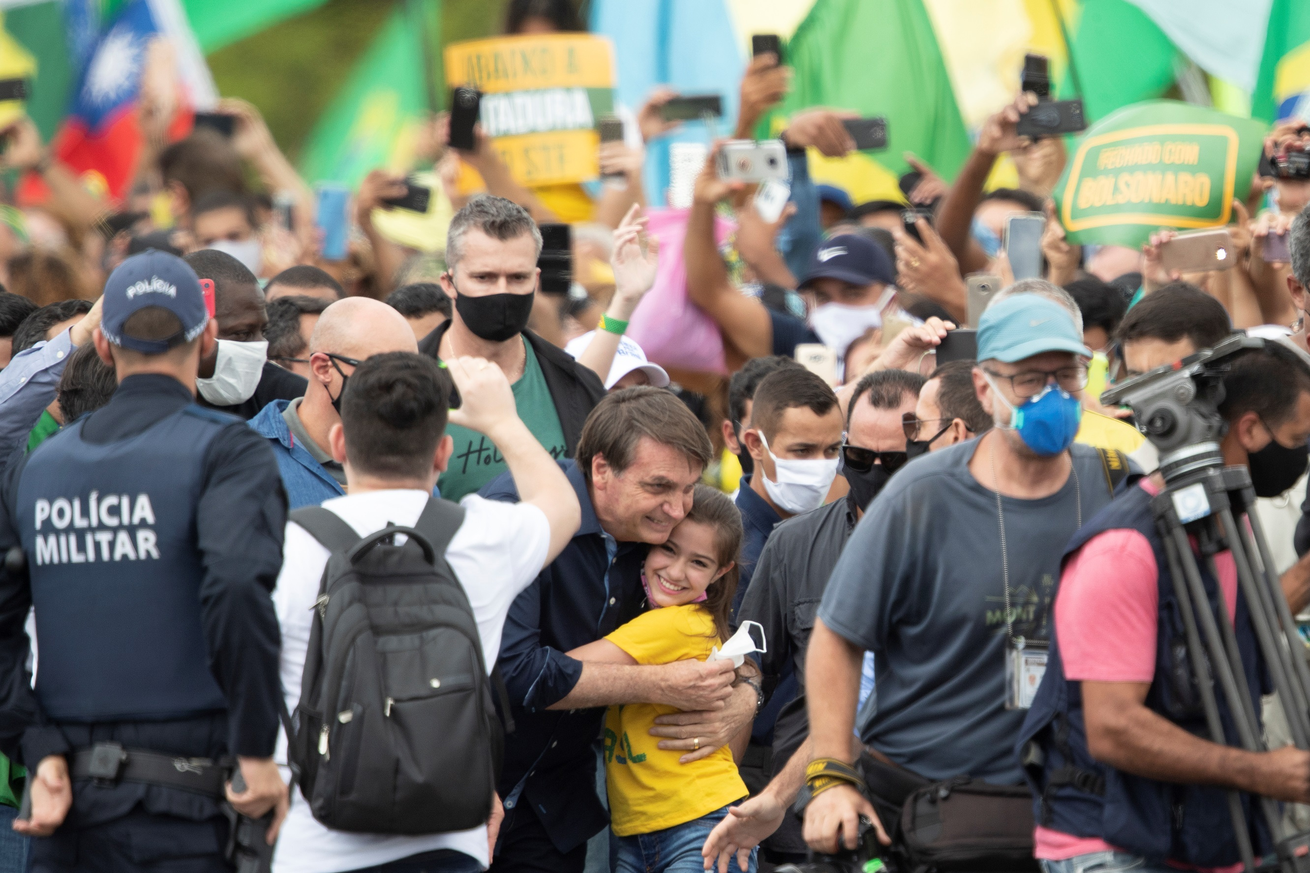 El presidente de Brasil, Jair Bolsonaro, saluda a una niña este domingo, en Brasilia (Brasil), sin ninguna medida de aislamiento social. EFE/Joédson Alves