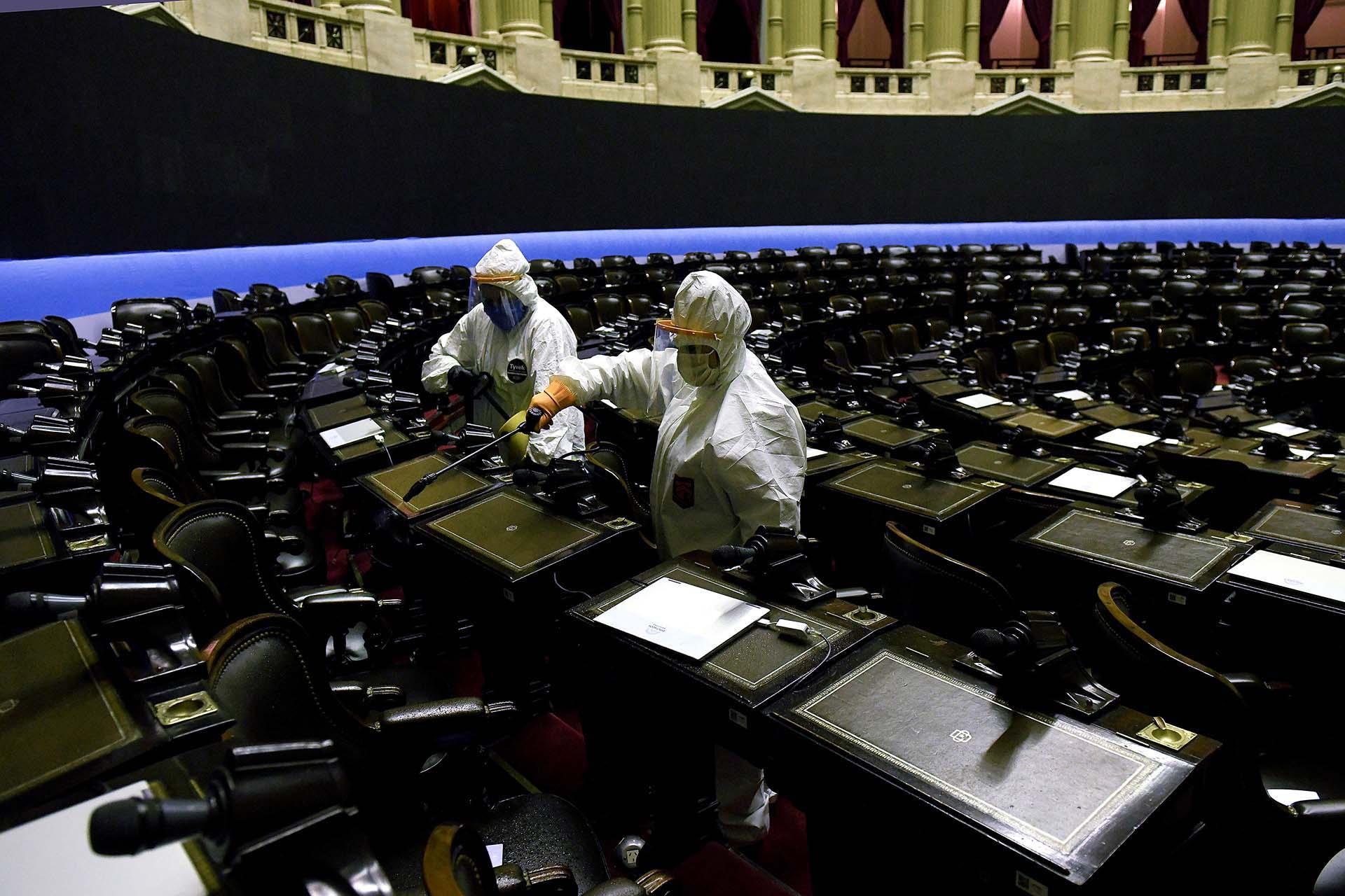 Empleados con equipo de protección desinfectan el recinto de la Cámara de Diputados
