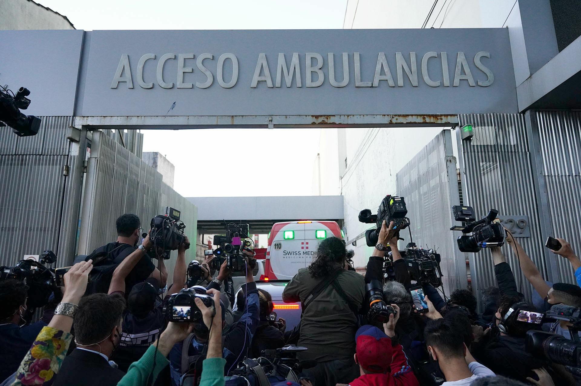 Una pared de fotógrafos y cámaras toman el ingreso de la ambulancia a la Clínica Olivos