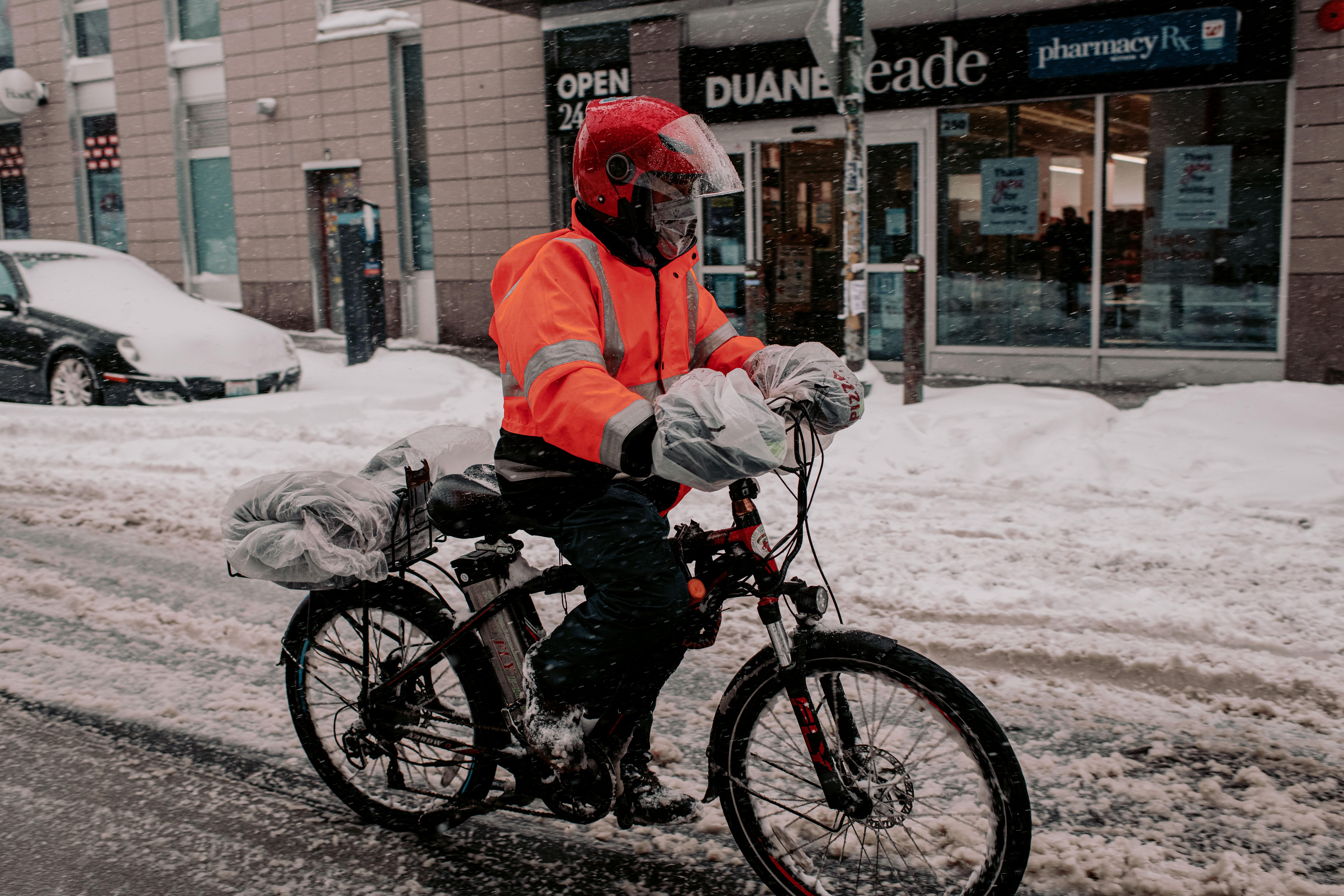 Un repartidor circula con su bicicleta por una calle llena de nieve en Brooklyn (Scott Heins/Getty Images/AFP)