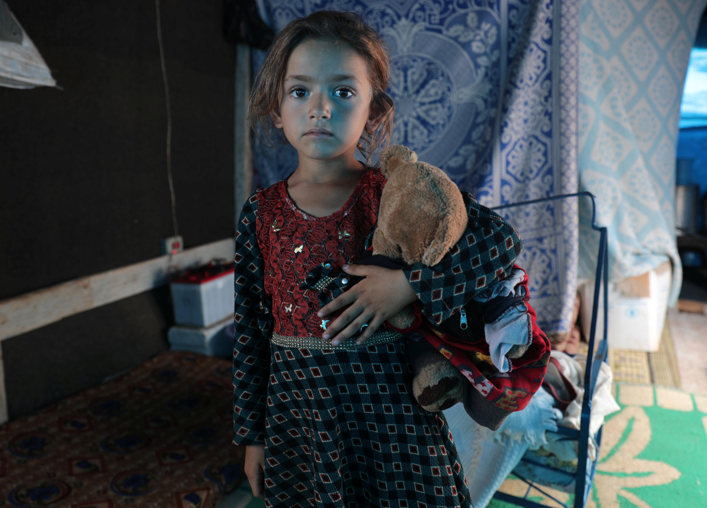 """Rawan al-Aziz, una niña siria de seis años, posa para una foto en una tienda de campaña en el campamento de Atmeh. Dijo que todavía recuerda su casa """"construida a la antigua usanza"""" en el sur de Idlib. """"Una casa para mí es un lugar donde están mis amigos y familiares. Traje mis juguetes conmigo, pero no es nada agradable aquí"""", dijo. """"Una carpa de campaña no es una casa, porque podría incendiarse y volar con el viento"""". (REUTERS / Khalil Ashawi)"""
