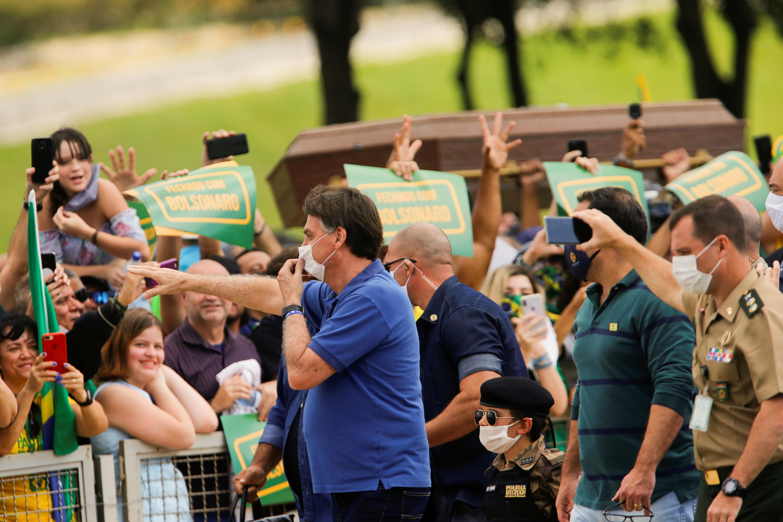 Esta vez con máscara facial, aunque visiblemente incomodo, el presidente Jair Bolsonaro saluda a sus seguidores en Brasilia, el 17 de mayo pasado. REUTERS/Adriano Machado