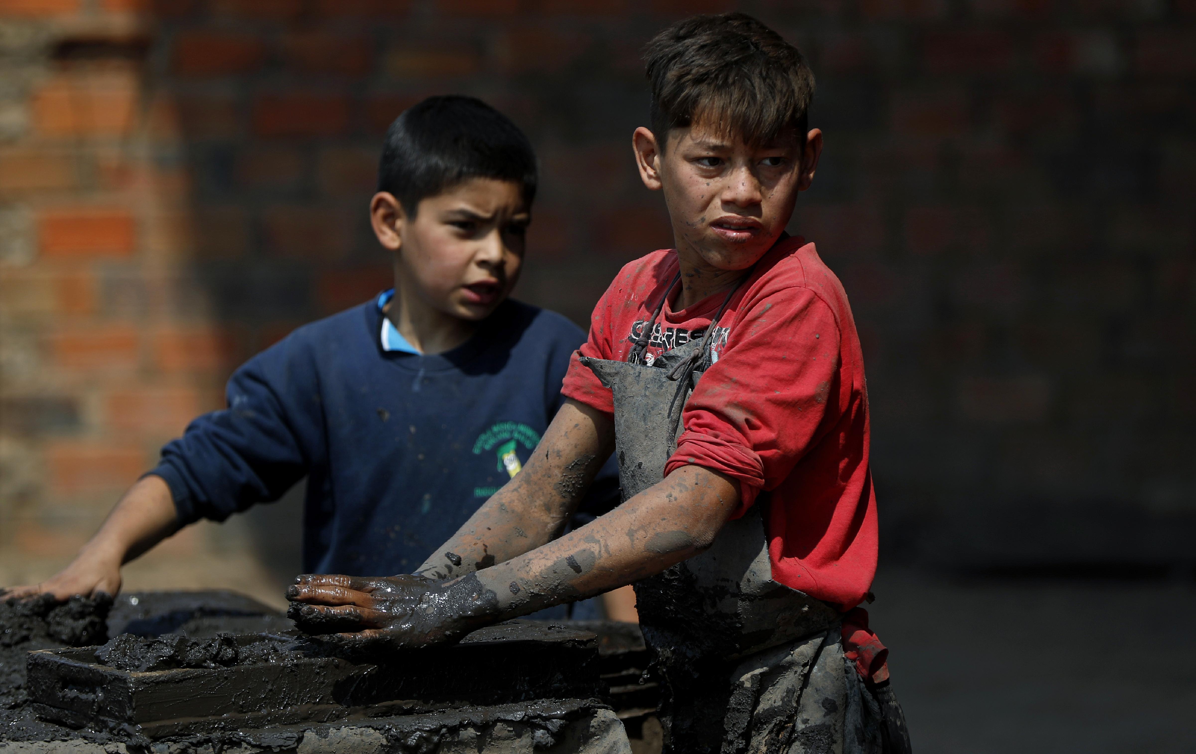 Mauri, 11, izquierda, y Cesar, 13, trabajan en una fábrica de ladrillos de arcilla en Tobati, Paraguay, el viernes 4 de septiembre de 2020.
