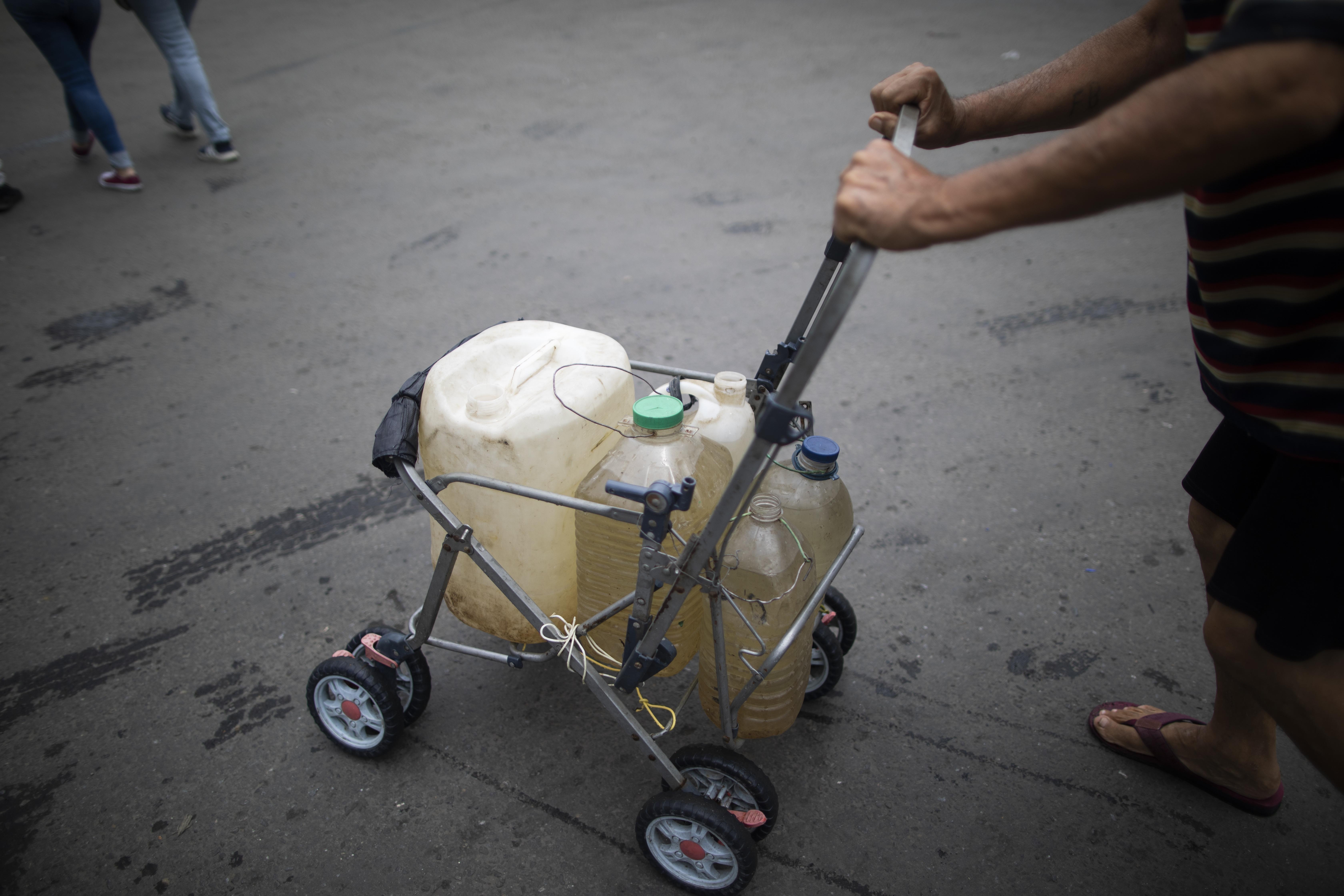 Un hombre empuja el armazón de un carrito de bebé con recipientes que llenó de agua en un grifo callejero, en Caracas, Venezuela, el 20 de junio de 2020. El suministro de agua en Venezuela es tan precario que en vecindarios pobres empiezan a gestionar canalizaciones privadas o a excavar pozos poco profundos. (AP Foto/Ariana Cubillos)