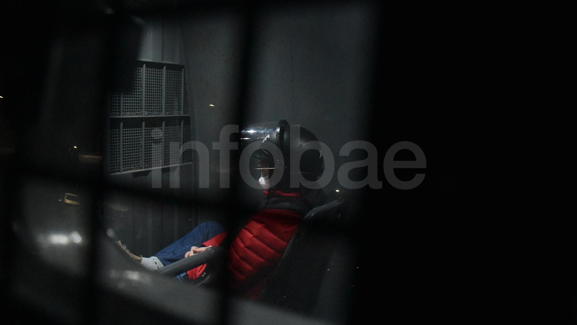 Báez sentado en la camioneta del SPF, vestido con el uniforme de los detenidos, chaleco y casco de protección