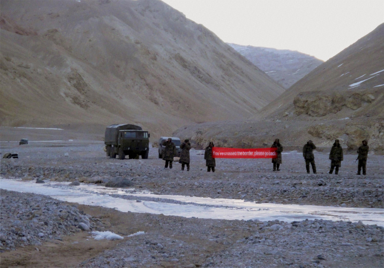 En esta imagen de archivo, tropas chinas despliegan una bandera que dice