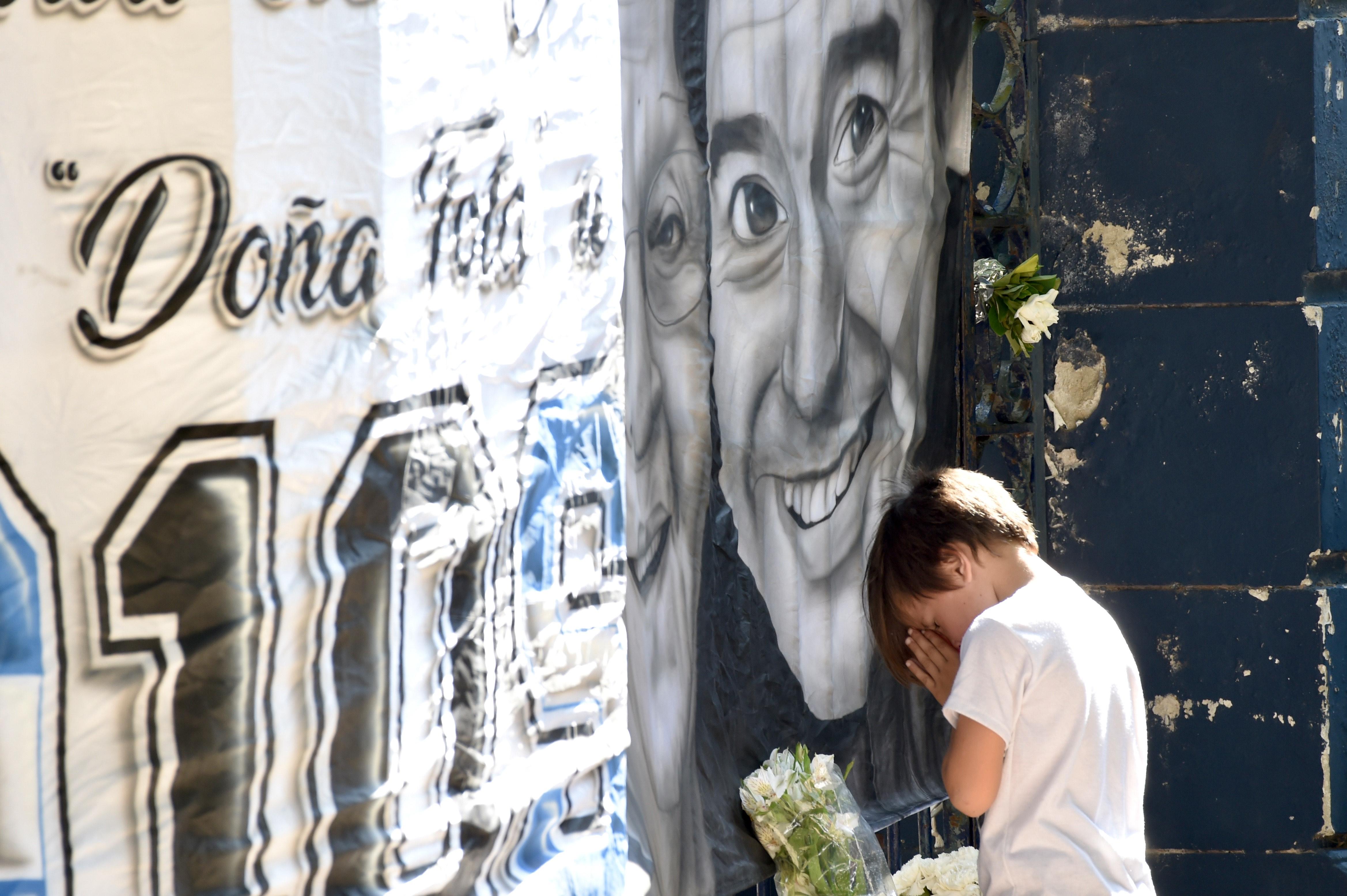 Un niño le reza a la imagen de Maradona junto a Doña tota en La Plata. Una de las fotos más impactantes del día (aglaplata)