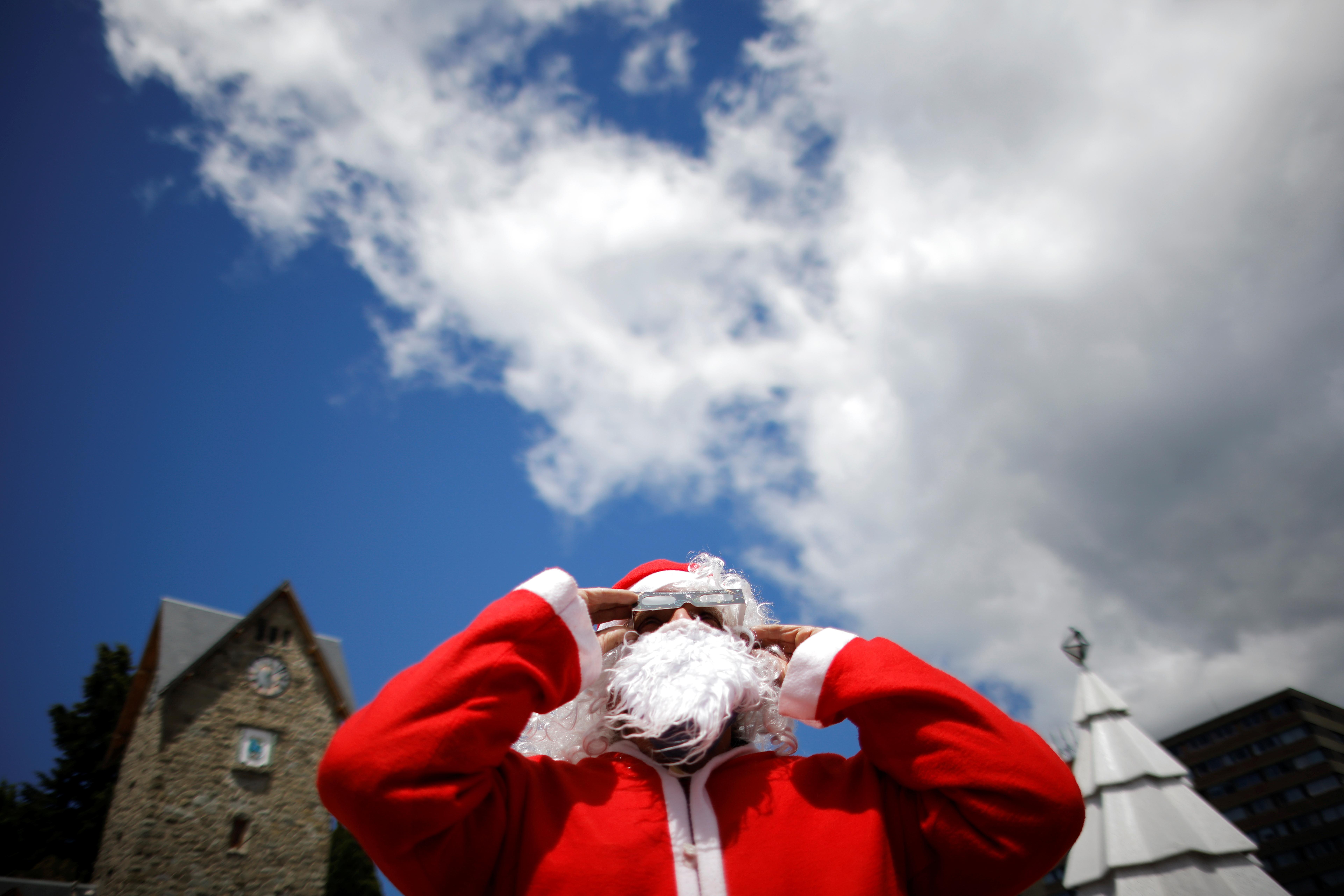 Un papa Noel en Bariloche con lentes especiales para seguir el eclipse