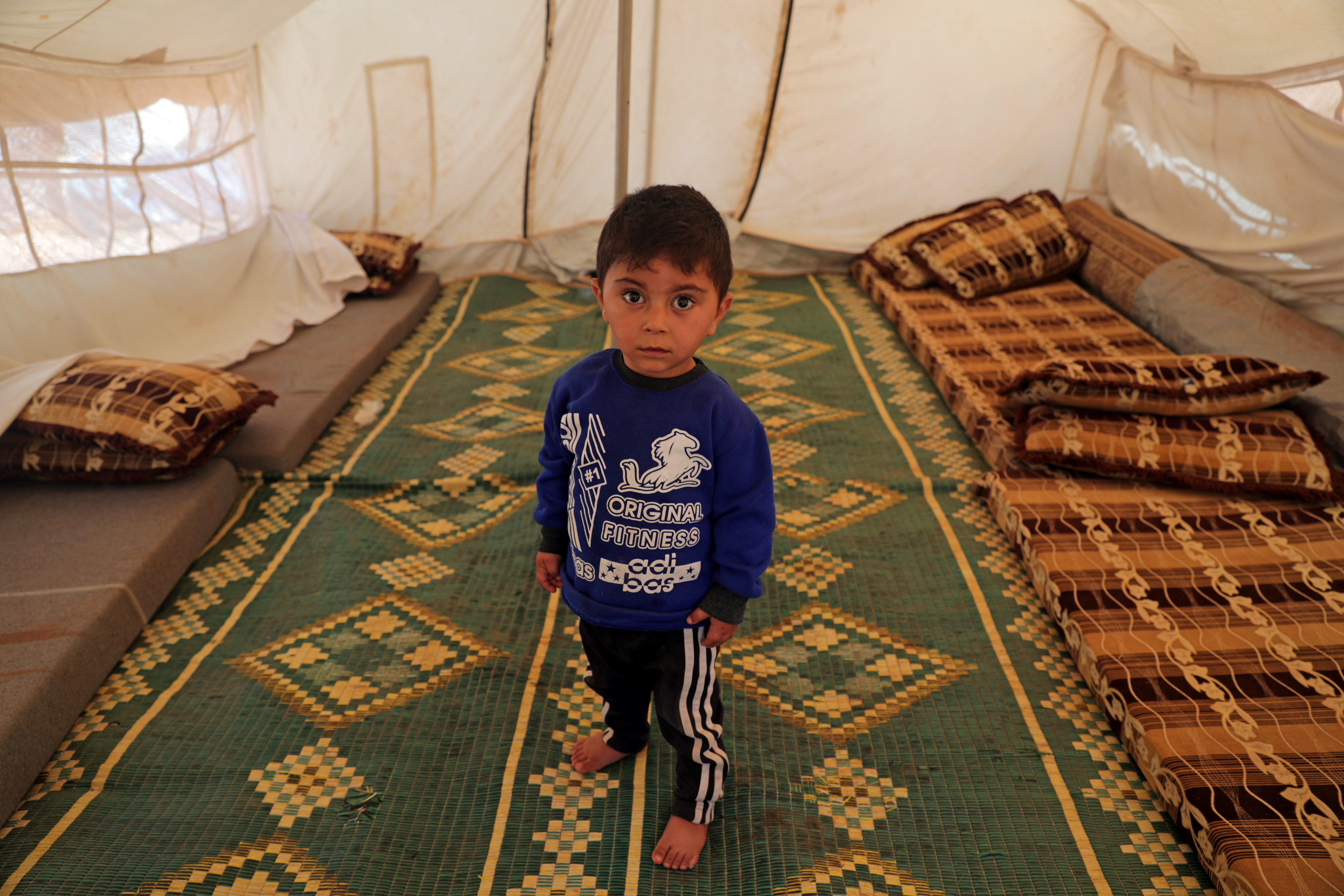 Walid al-Khaled, un niño desplazado sirio de 2 años de la ciudad de Alepo, posa para una foto en una tienda de campaña en el campamento de Atmeh (REUTERS / Khalil Ashawi)