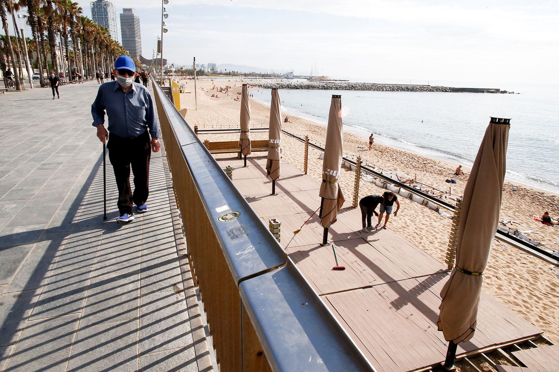 Varios trabajadores de un chiringuito de la playa de la Barceloneta preparan el local, este lunes en Barcelona que ha entrado en la Fase 1 de la descalada. (EFE/ Quique García)