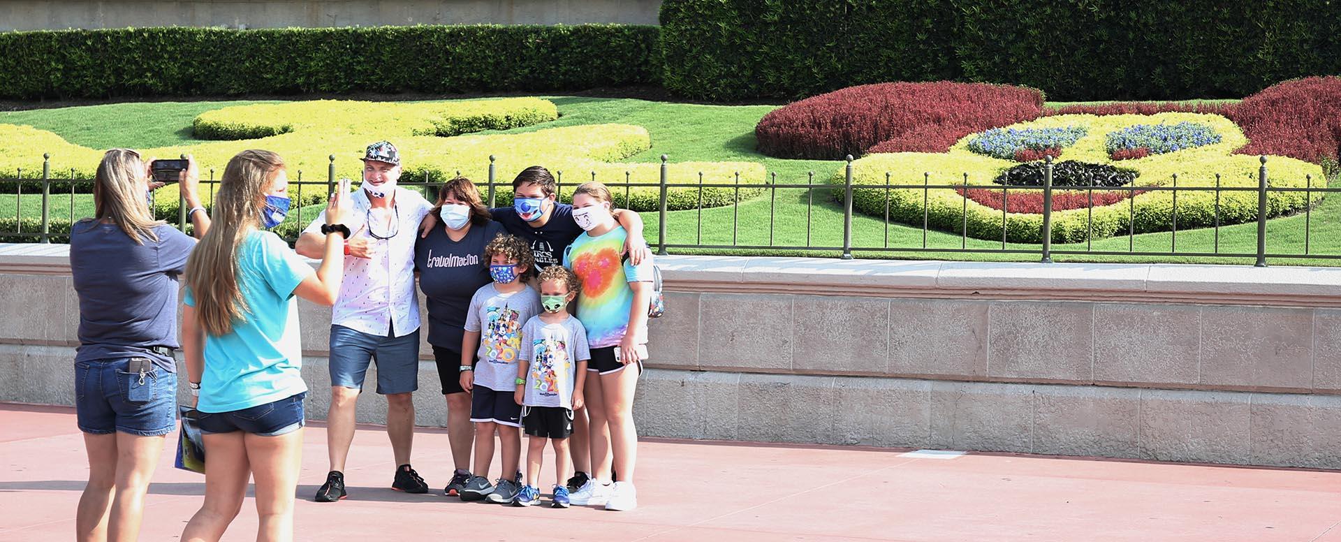 Una familia posa, todos con mascarilla, frente a un paisaje en forma de Mickey