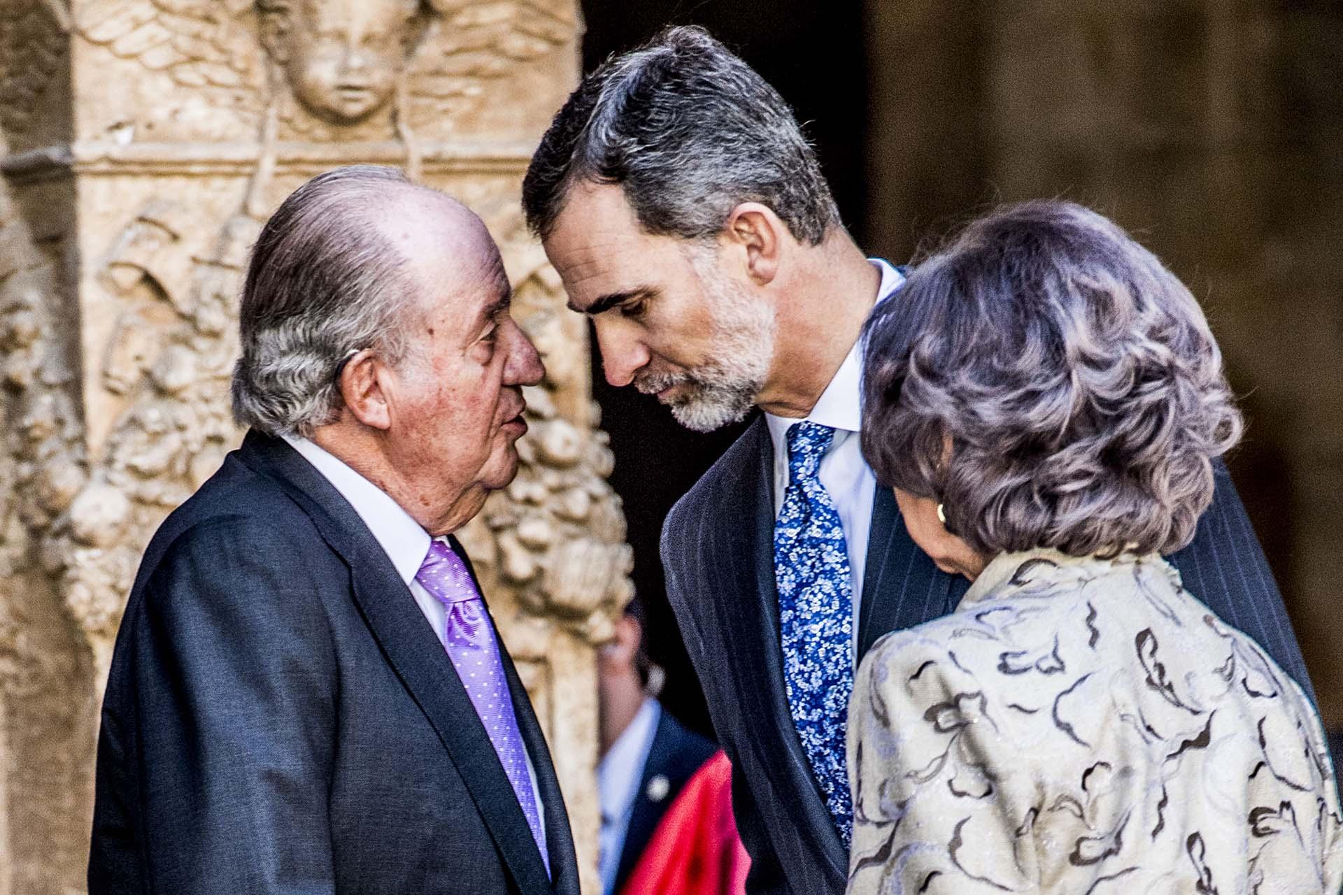 El rey emérito junto a su hijo, Felipe y su madre Sofía, de espaldas, en Palma de Mallorca, en una de las últimas imágenes de ambos juntos (Shutterstock)
