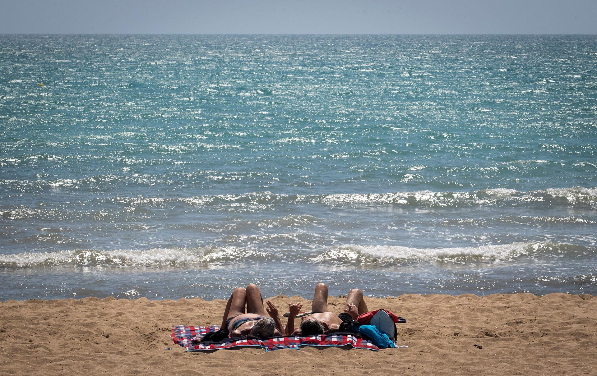 Dos turistas tomando solo en la playa de Palma de Mallorca.