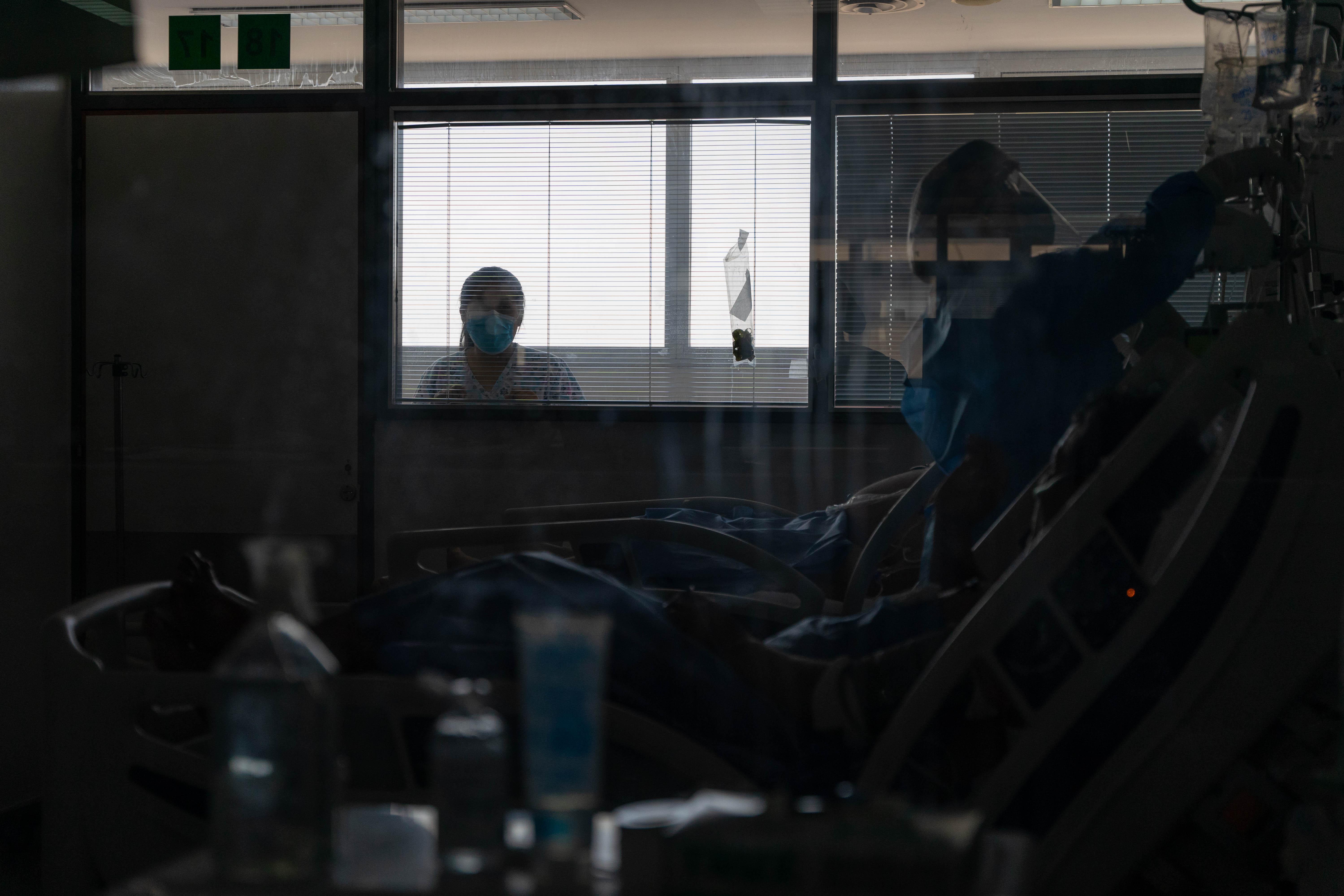 Una enfermera del hospital mira a su padre, internado en la UTI Covid.