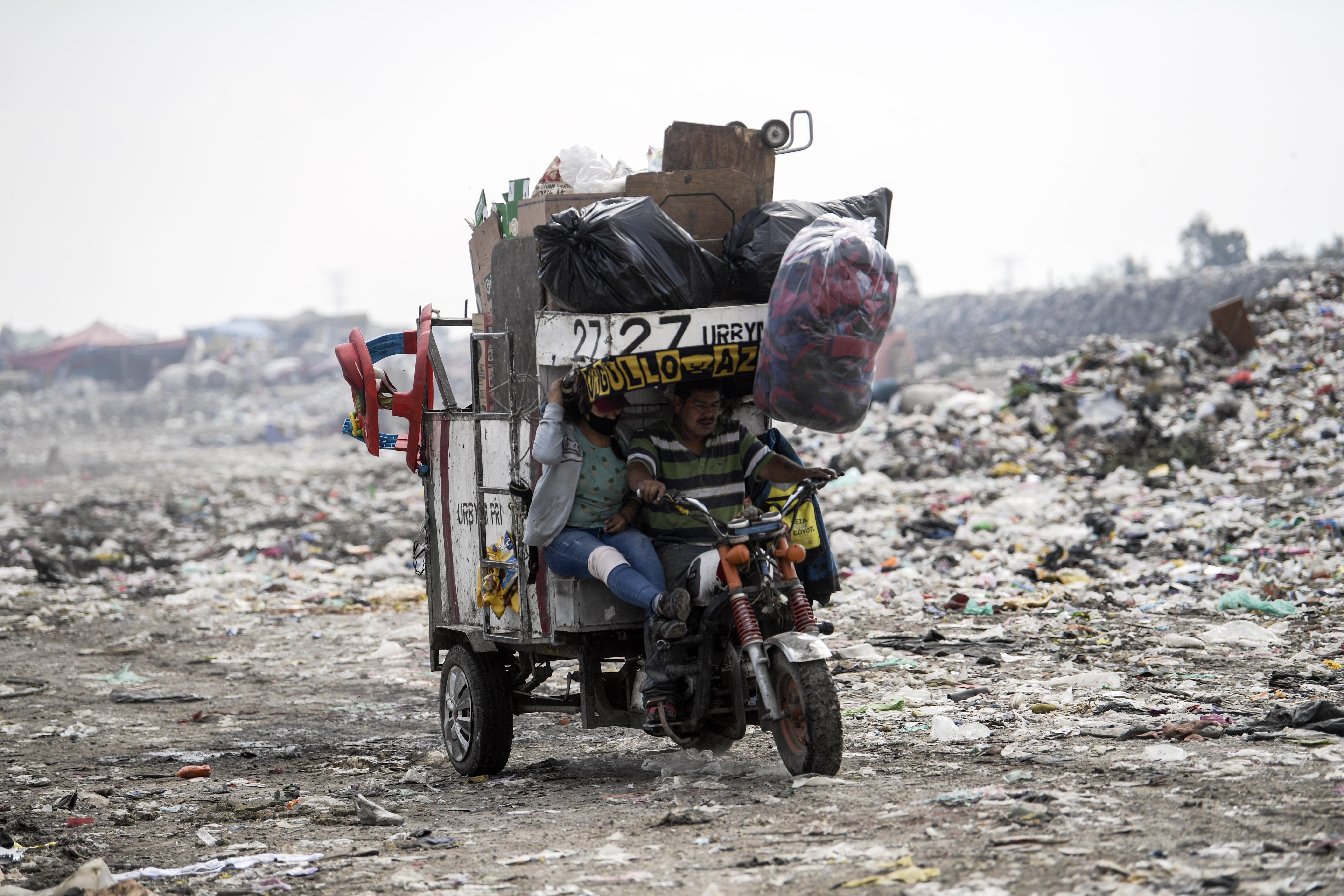 Una pareja viaja en un triciclo a motor en el basurero