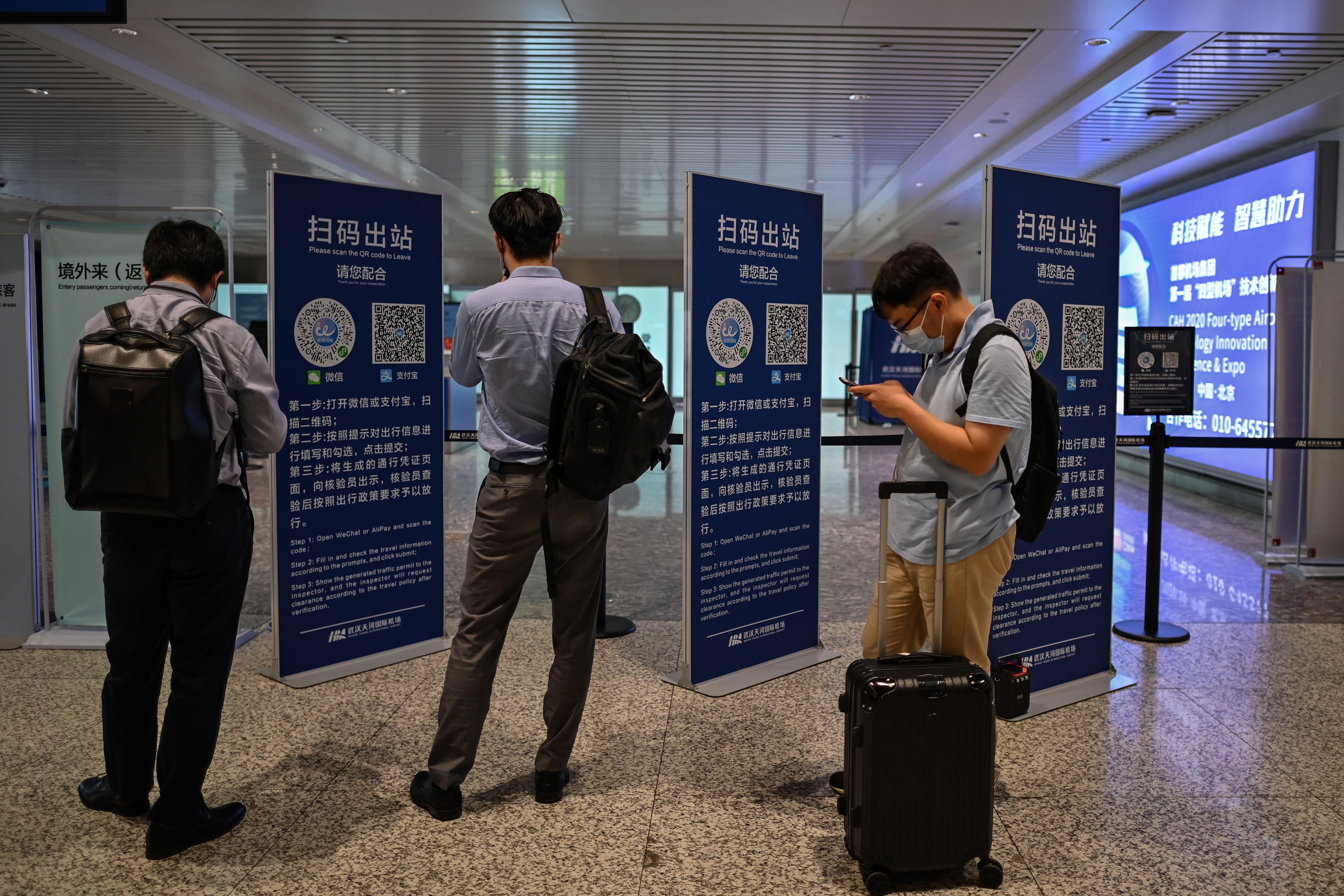 Pasajeros revisan los códigos de salud en la zona de llegadas del aeropuerto Tianhe en Wuhan