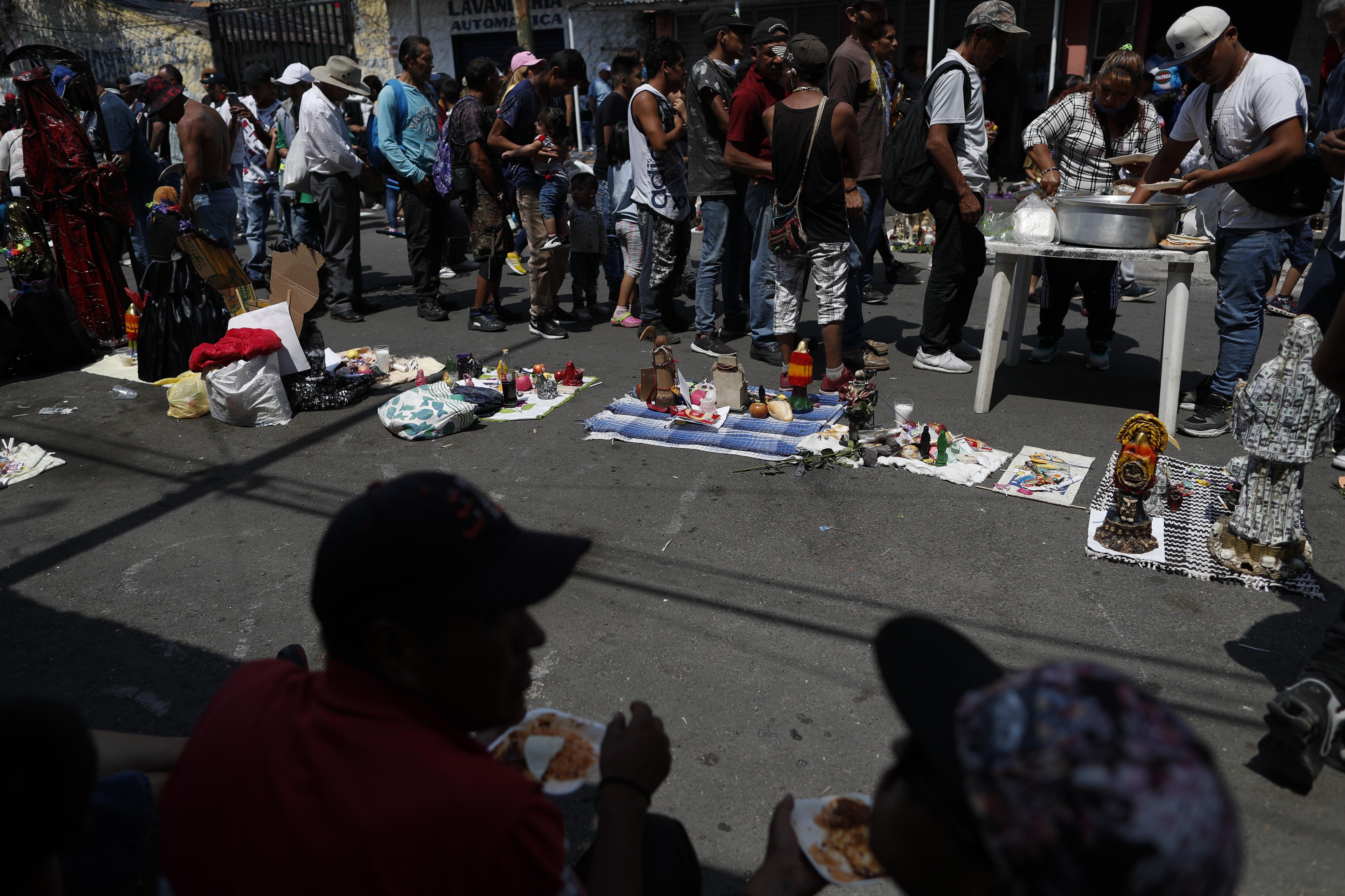Los devotos de la Santa Muerte hacen cola para recibir un almuerzo donado, frente a un altar en el barrio de Tepito de la Ciudad de México, el lunes 1 de junio de 2020. (Foto: AP / Rebecca Blackwell)