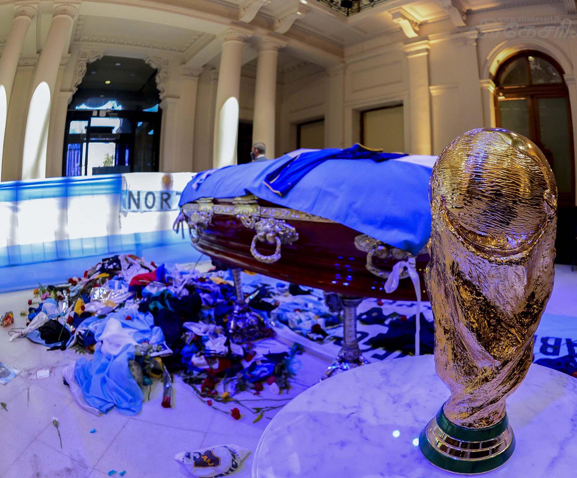 El cajón con el cuerpo de Diego Armando Maradona en el Salón Presidencial de la Casa Rosada. La Copa del Mundo. Las banderas argentinas. Y las ofrendas de los hinchas. Todo en una foto