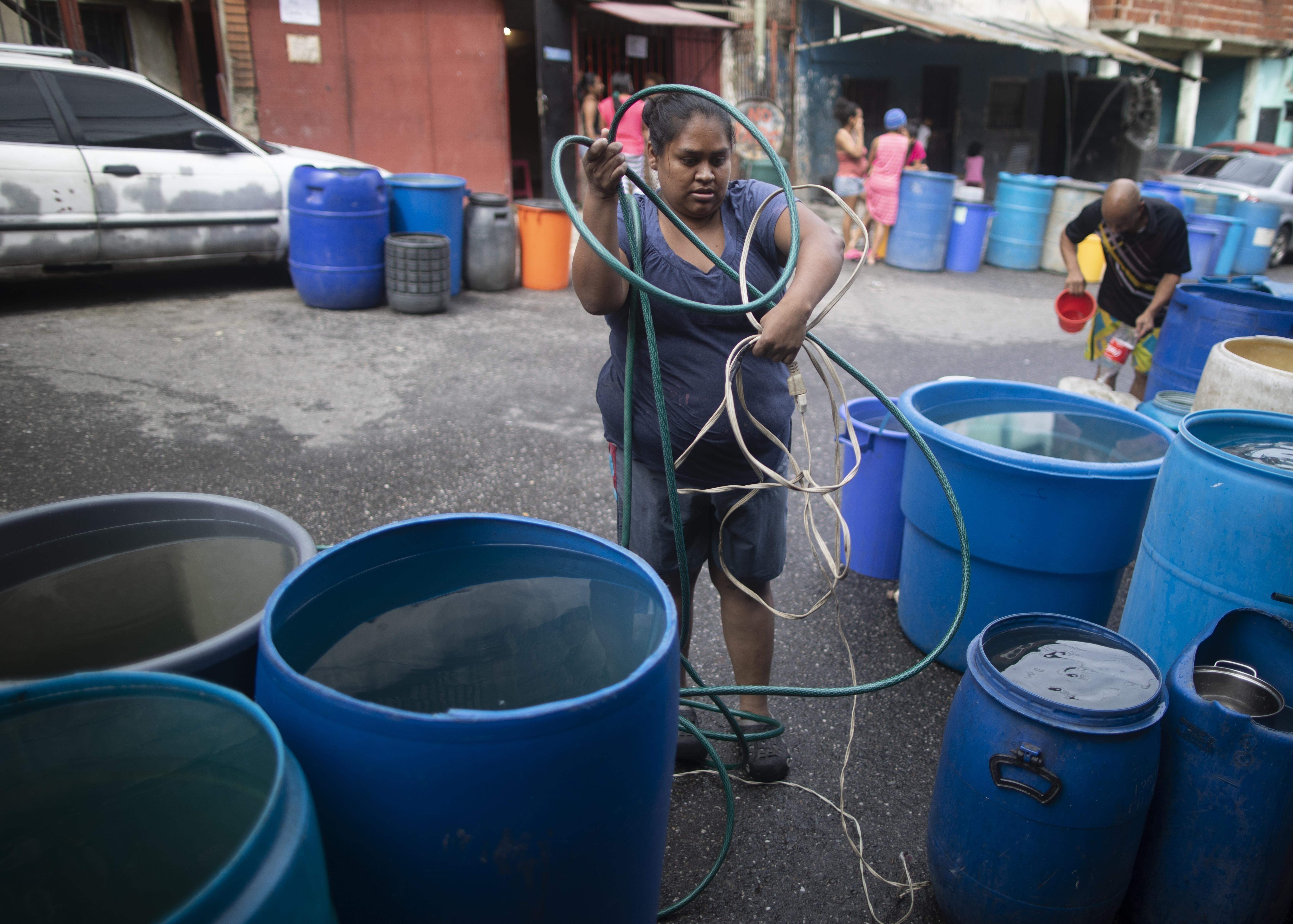 Una mujer desenreda un cable eléctrico y una manguera para bombear agua desde un gran recipiente proporcionado por un camión cisterna del gobierno, en el vecindario humilde de Petare, en Caracas, Venezuela, el 10 de junio de 2020. La crisis de agua no es nada nuevo en Venezuela, pero el agua es todavía más importante hoy en día para protegerse de la pandemia del coronavirus. (AP Foto/Ariana Cubillos)