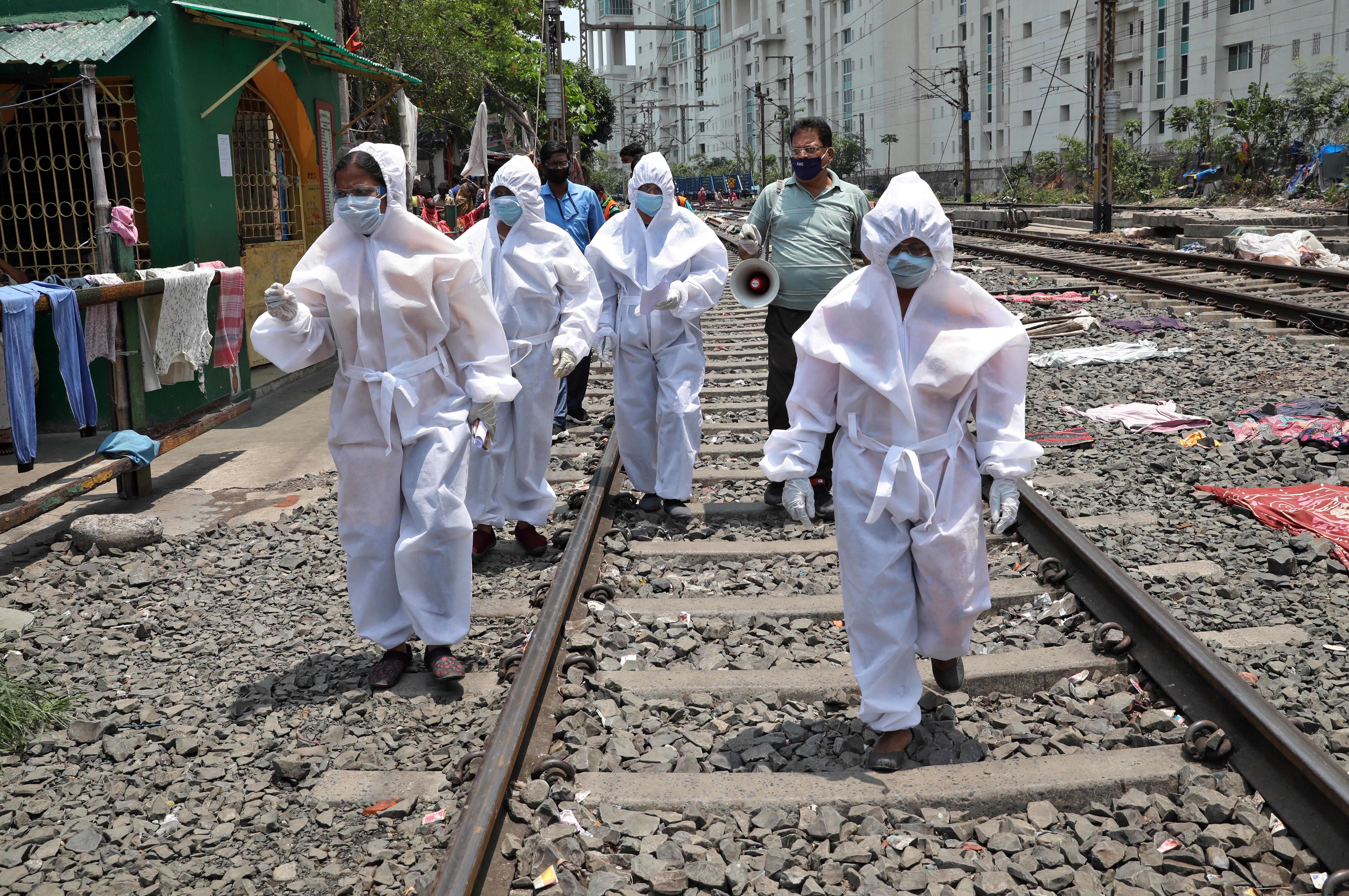 Trabajadores de la salud con equipo de protección caminan por una vía férrea al llegar a un área de tugurios para una verificación puerta a puerta de las personas para averiguar si han desarrollado alguno de los síntomas de la enfermedad coronavirus (COVID-19), en Calcuta, India, el 24 de abril de 2020. REUTERS/Rupak De Chowdhuri