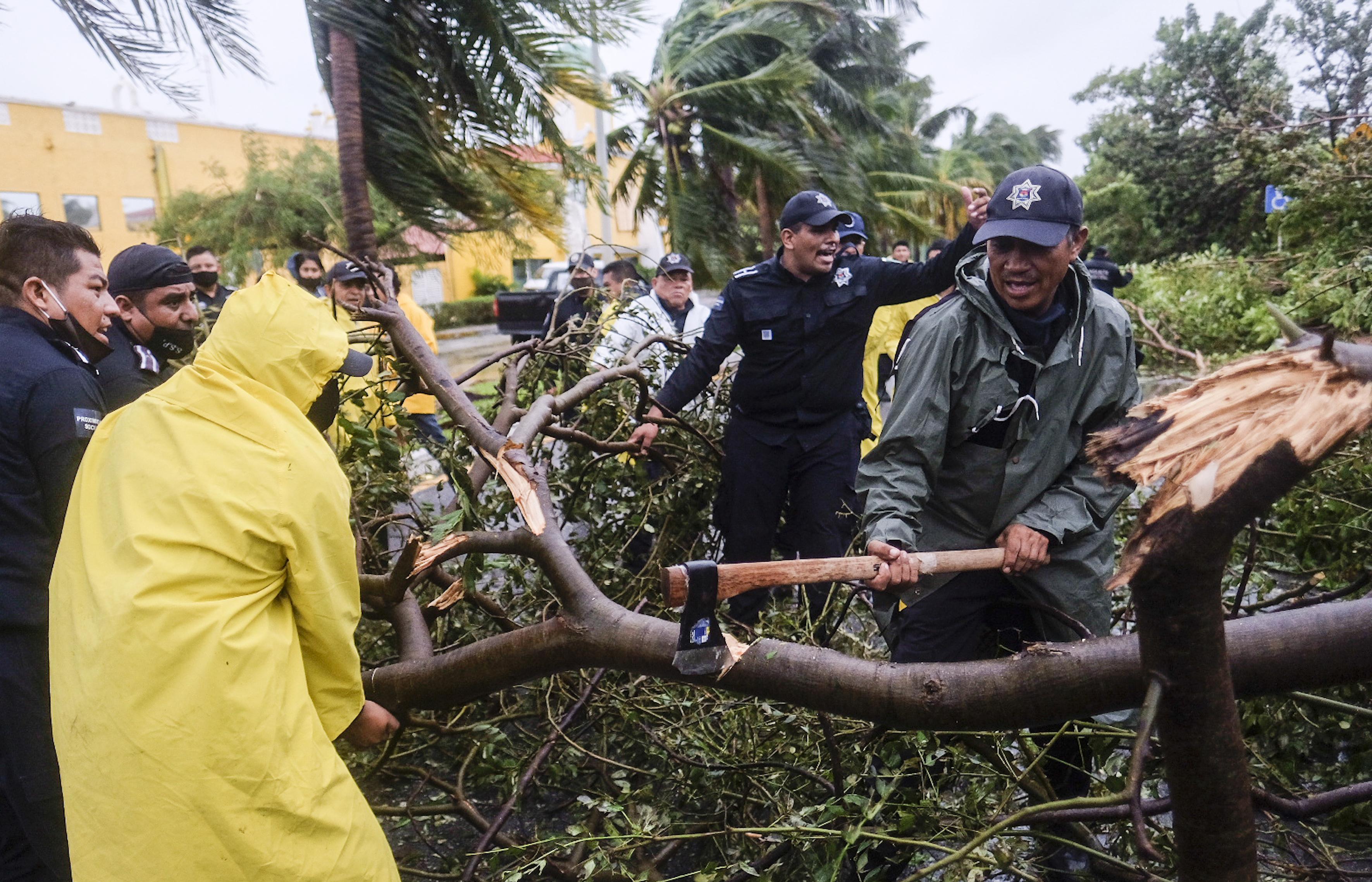 Los bomberos quitan un árbol derribado por el huracán Delta en Cancún, México, el miércoles 7 de octubre de 2020 temprano.