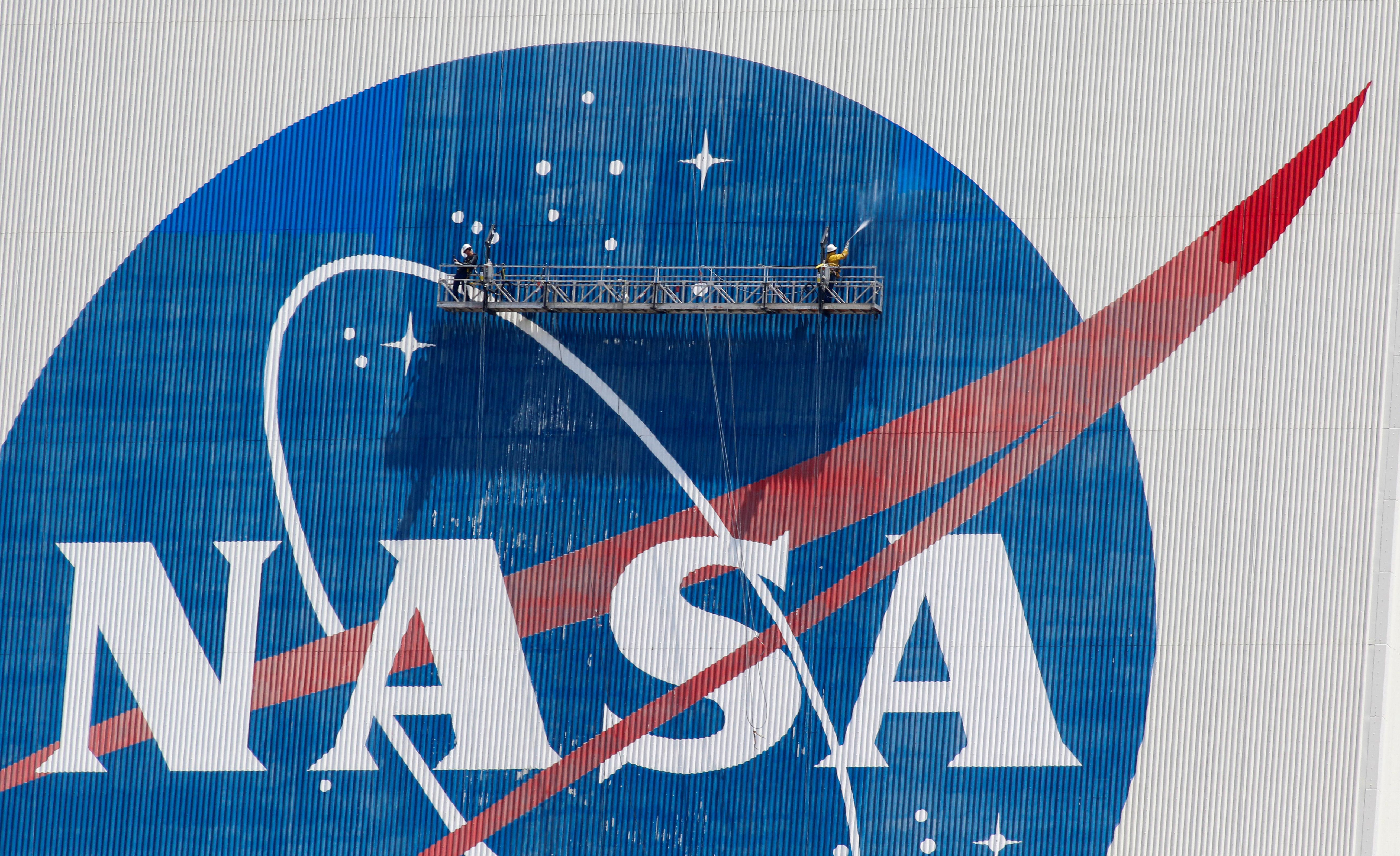 Trabajadores lavan a presión el logo de la NASA en el edificio de ensamblaje de vehículos antes de que SpaceX envíe dos astronautas de la NASA a la Estación Espacial Internacional (REUTERS/Joe Skipper/Foto de archivo)