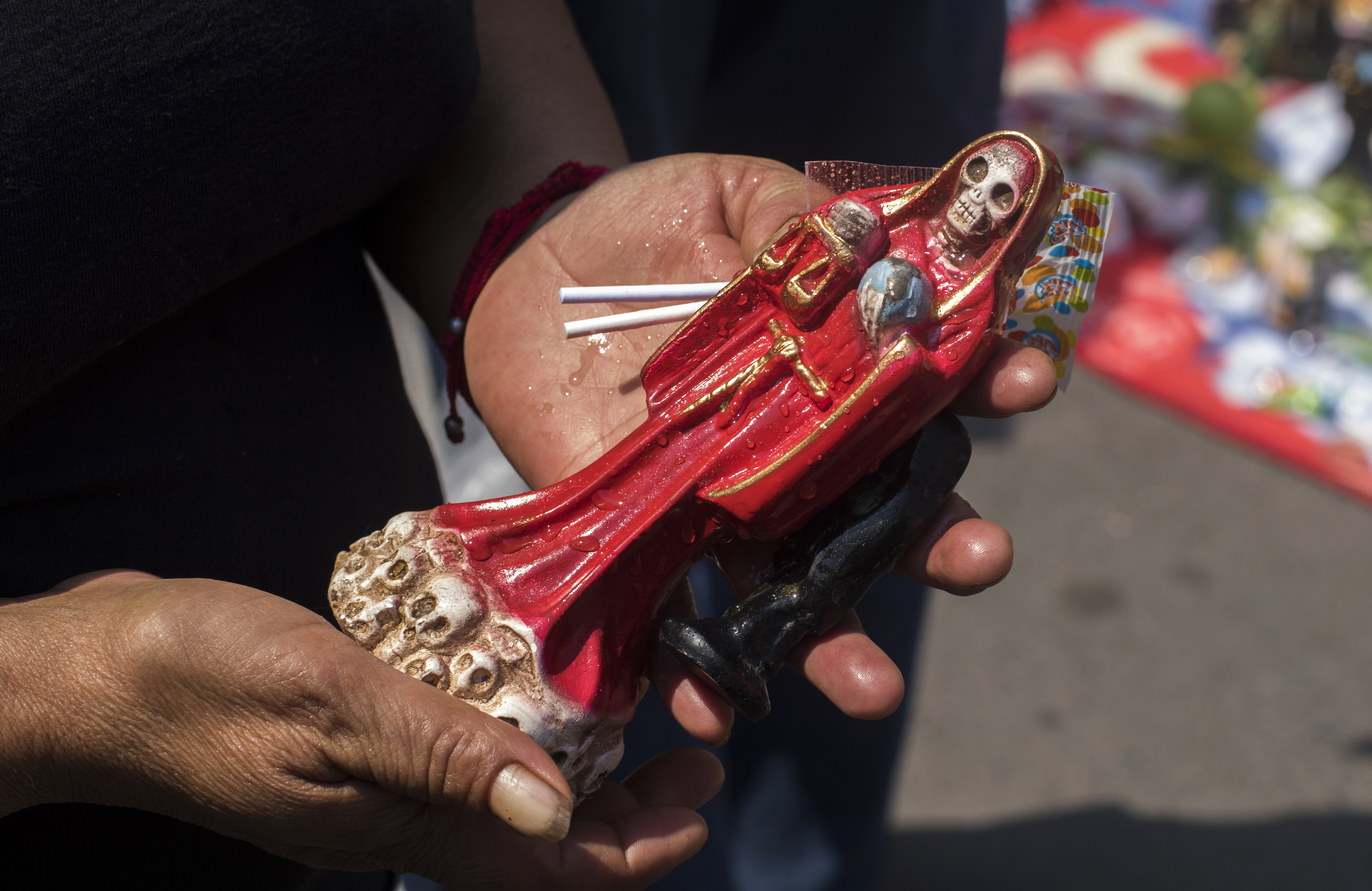 Un devoto sostiene una figura de la Santa Muerte frente a su santuario en la calle Alfarería, en el barrio de Tepito de la Ciudad de México, el 1 de octubre de 2020